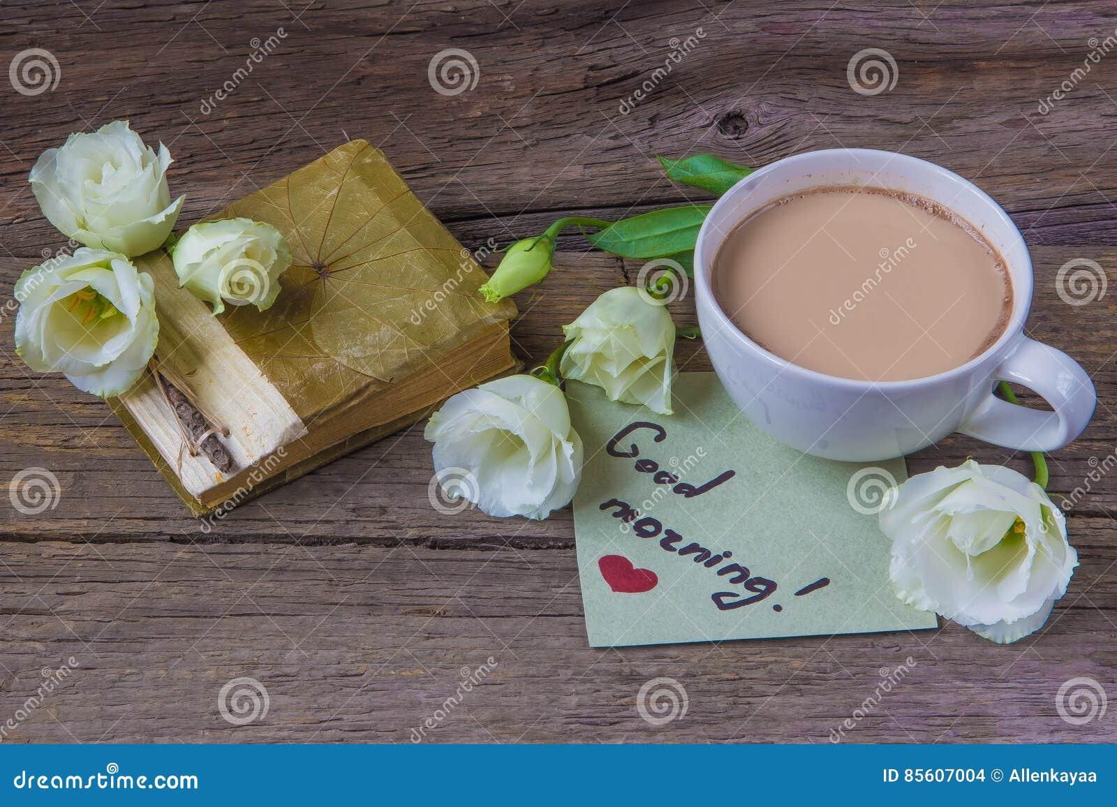 Copo de café com o lisianthus da flor da mola e o bom dia das notas
