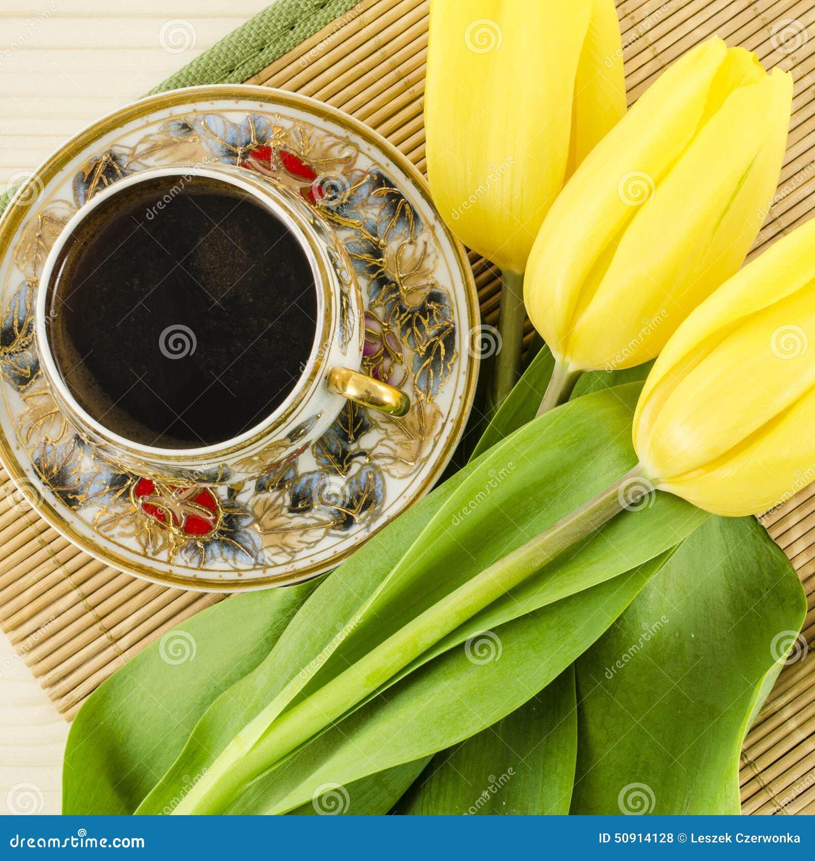 Copo de café da porcelana com as flores amarelas da tulipa