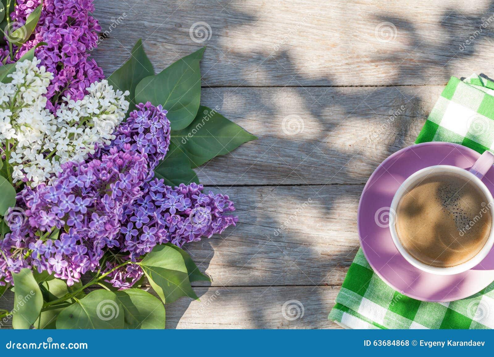 Copo de café e flores lilás coloridas na tabela do jardim