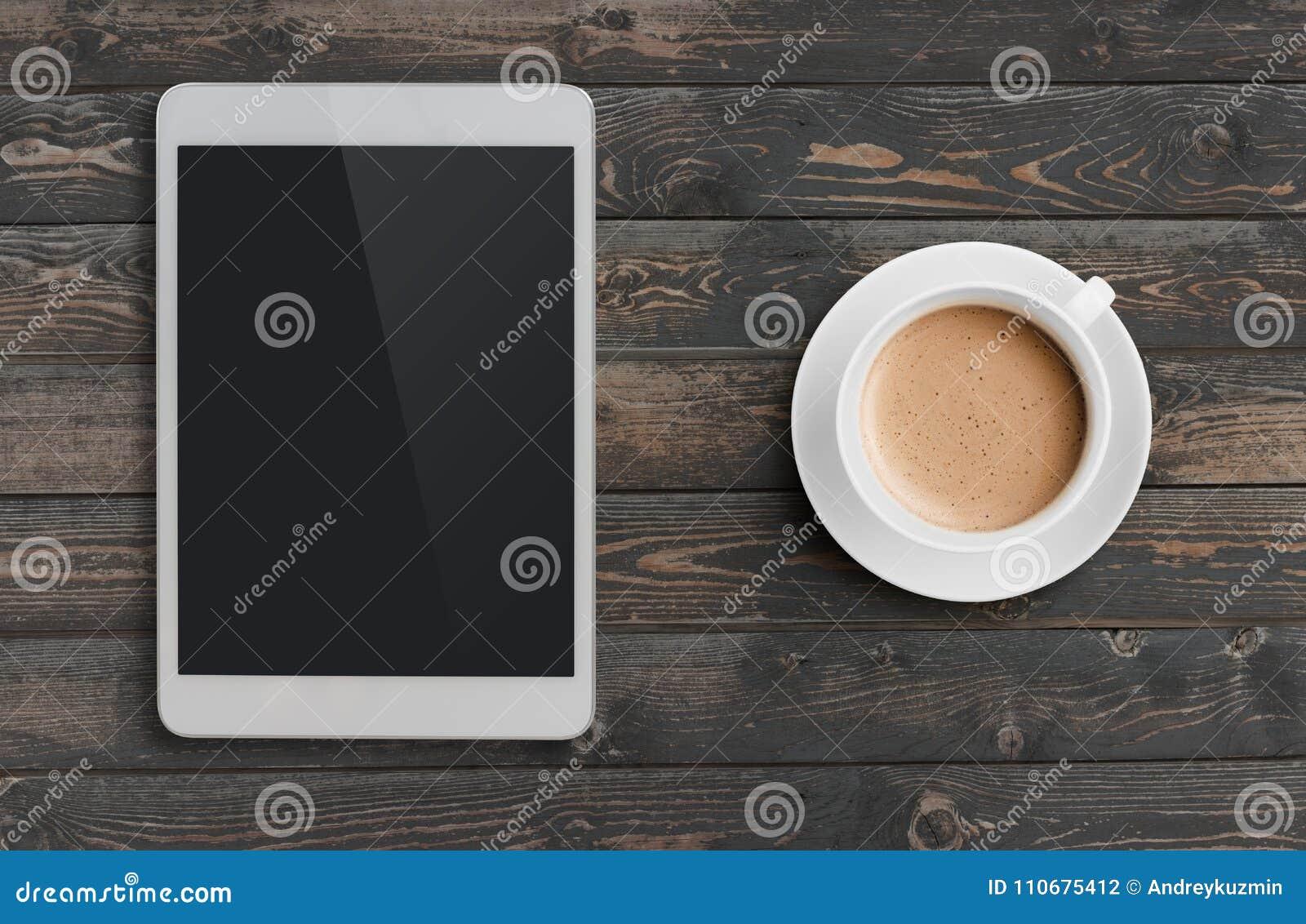 Copo de café e PC da tabuleta similar ao ipad na opinião de tampo da mesa de madeira escura