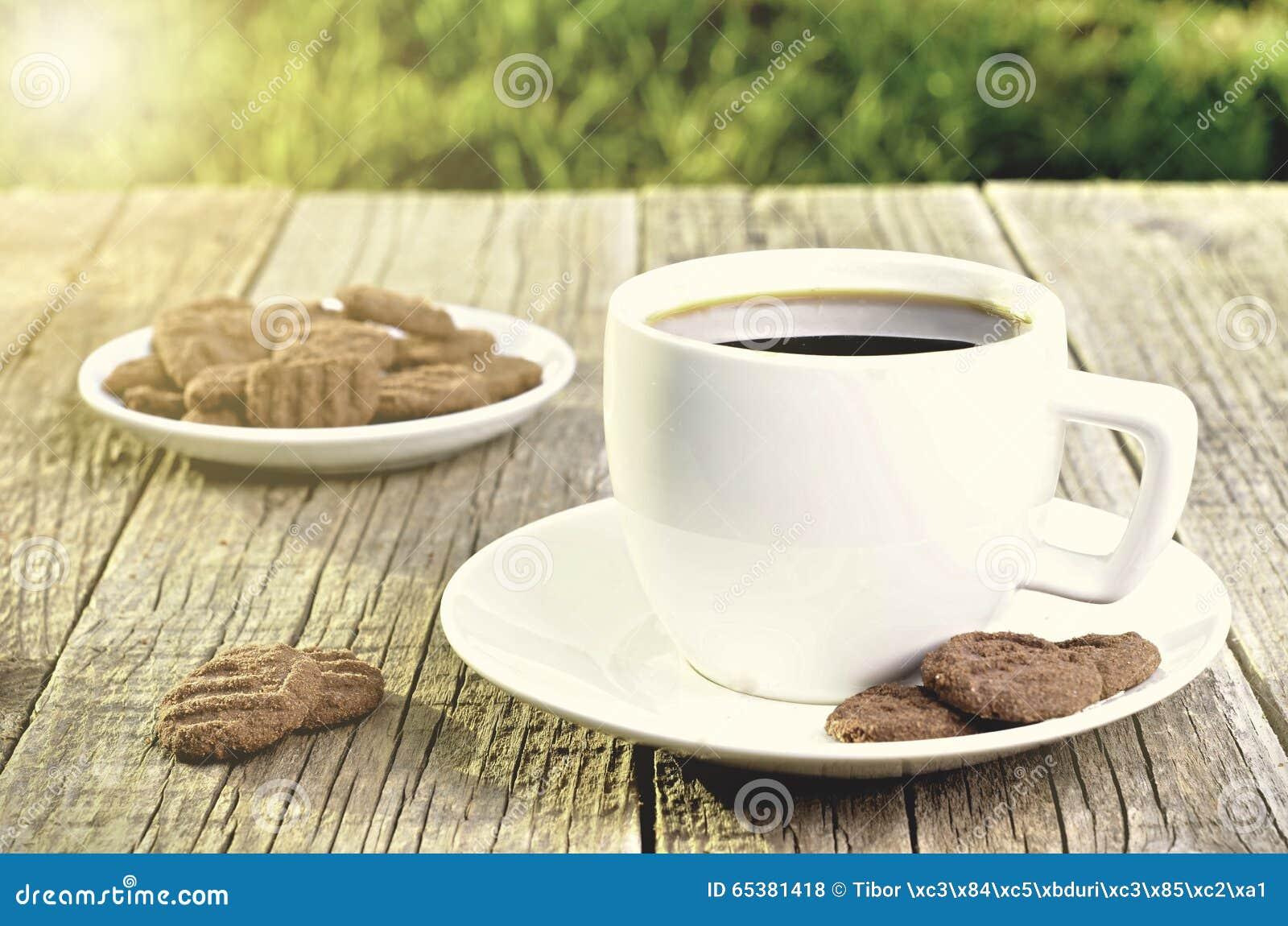 Copo de café no feijões Fundo dos feijões de café Copo branco Copo completo Agricultura e semente Luz natural