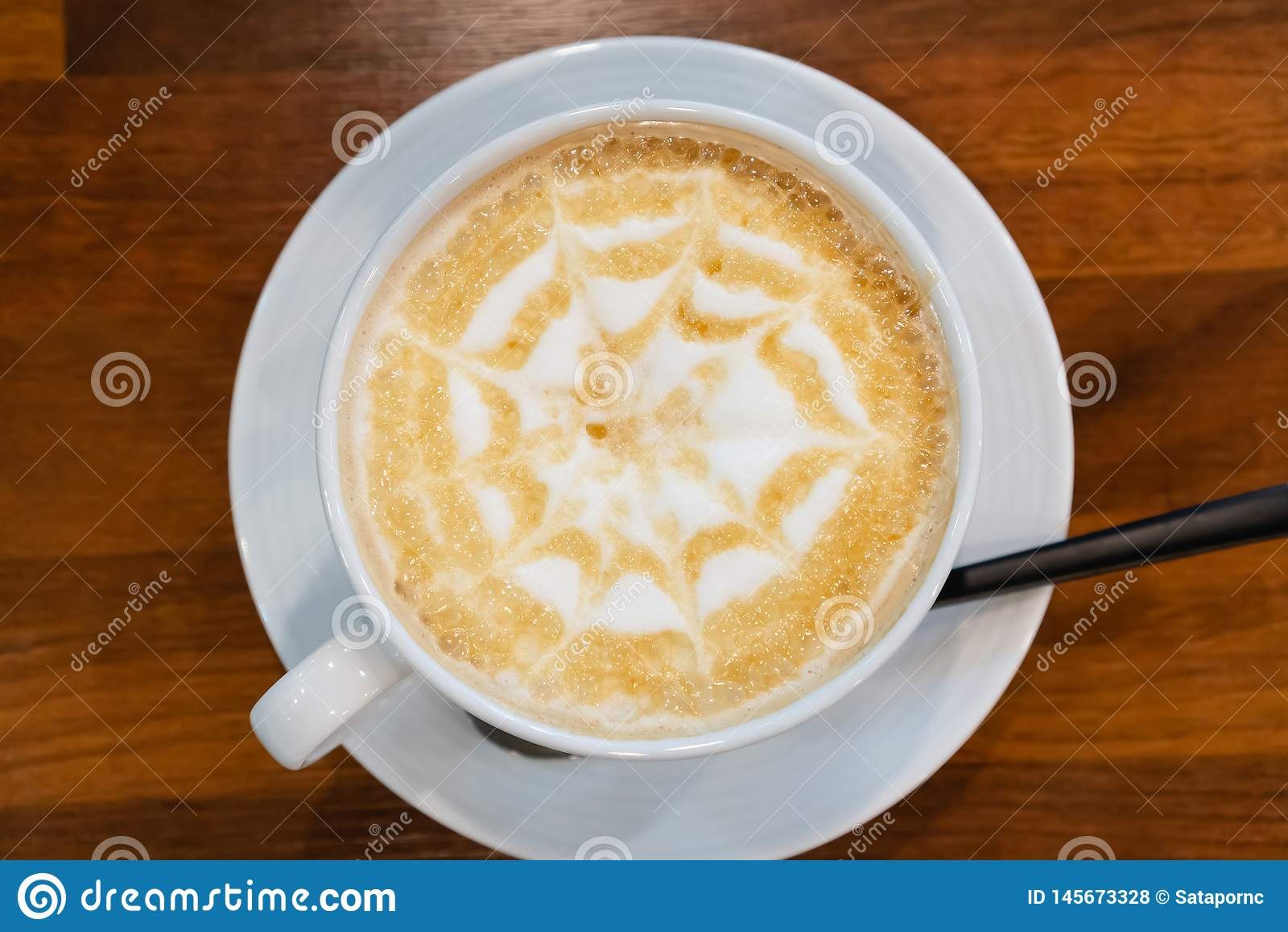 Copo de caf? com espuma da arte da forma da estrela no fundo de madeira da tabela no tampo da mesa no caf?