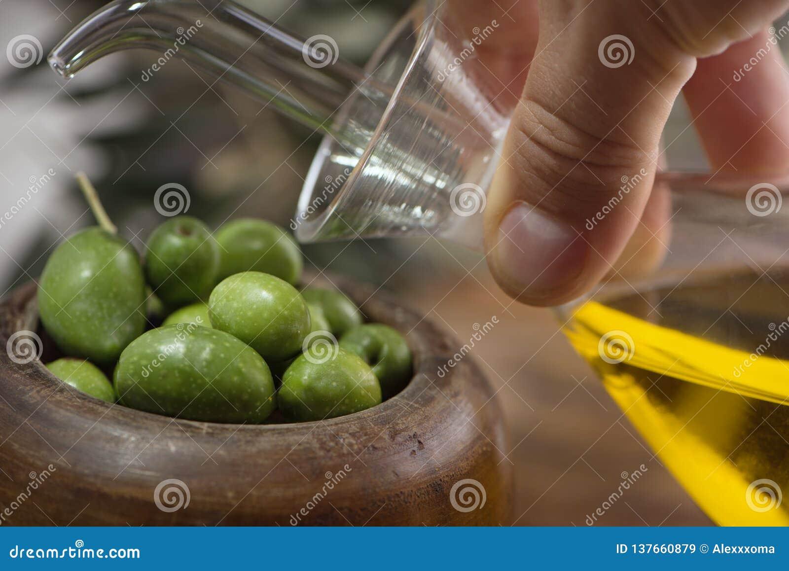 Copo de madeira das azeitonas com azeite virgem extra na garrafa de vidro na mão no fundo rústico Baixa chave