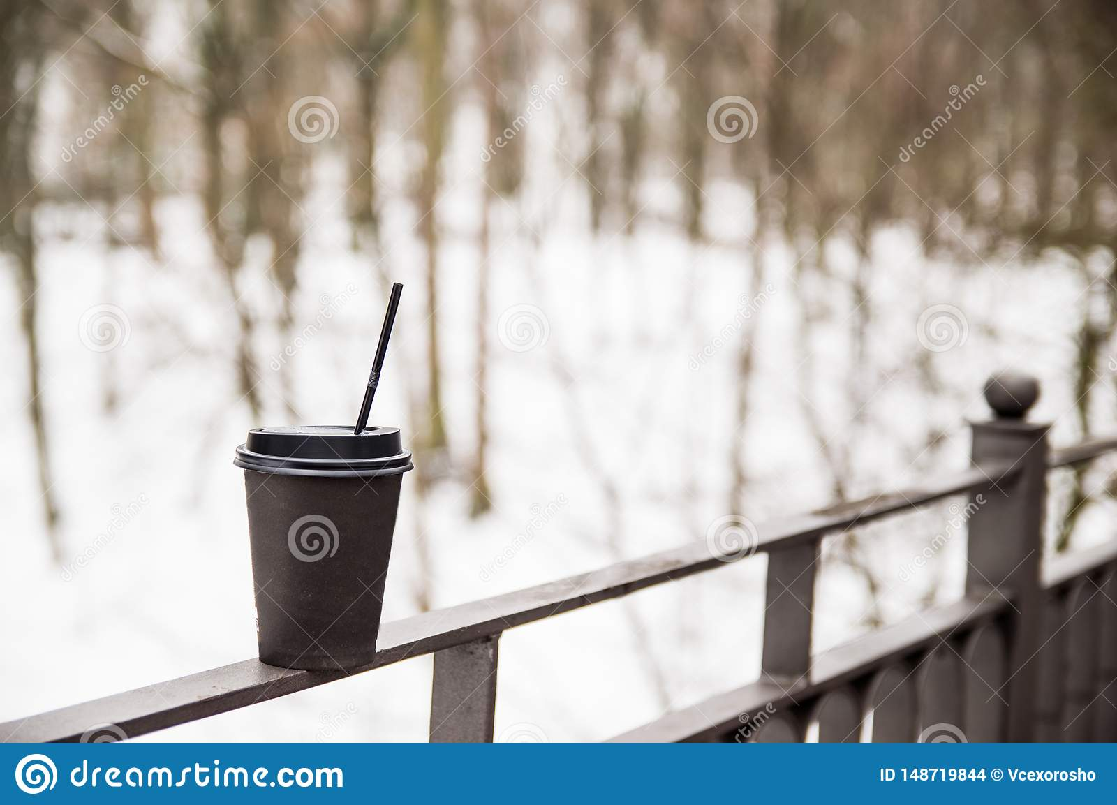 Copo de papel com suportes do caf? em um corrim?o do metal na ponte