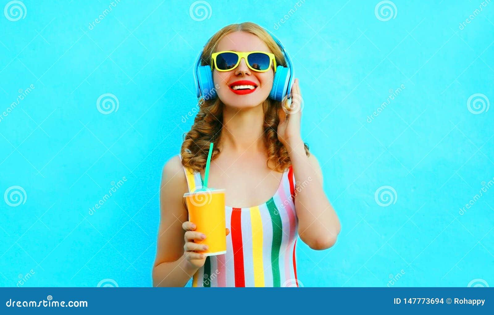 Copo de sorriso feliz da terra arrendada da mulher do suco que escuta a música em fones de ouvido sem fio no azul colorido