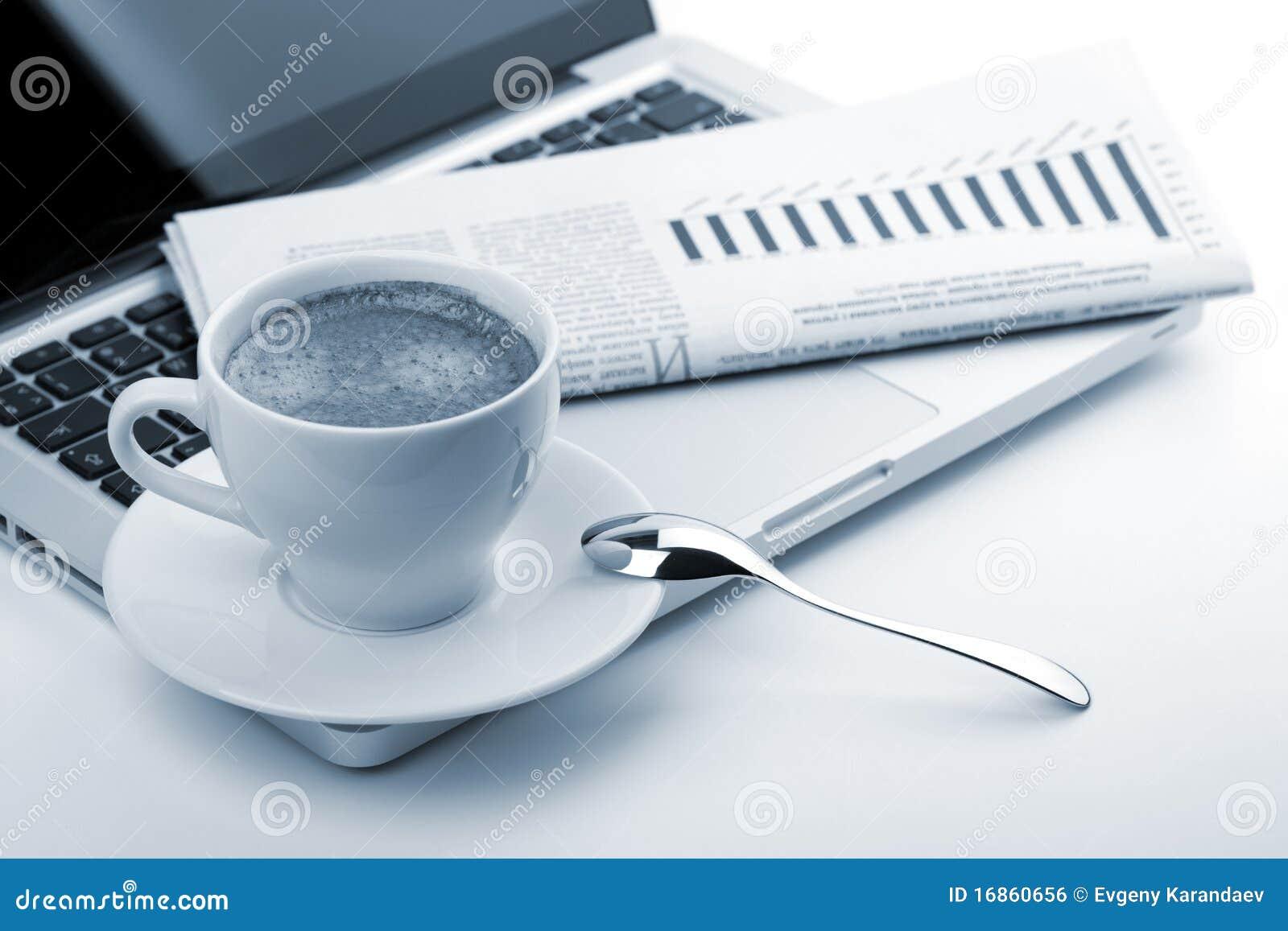 Copo do Cappuccino com portátil e jornal