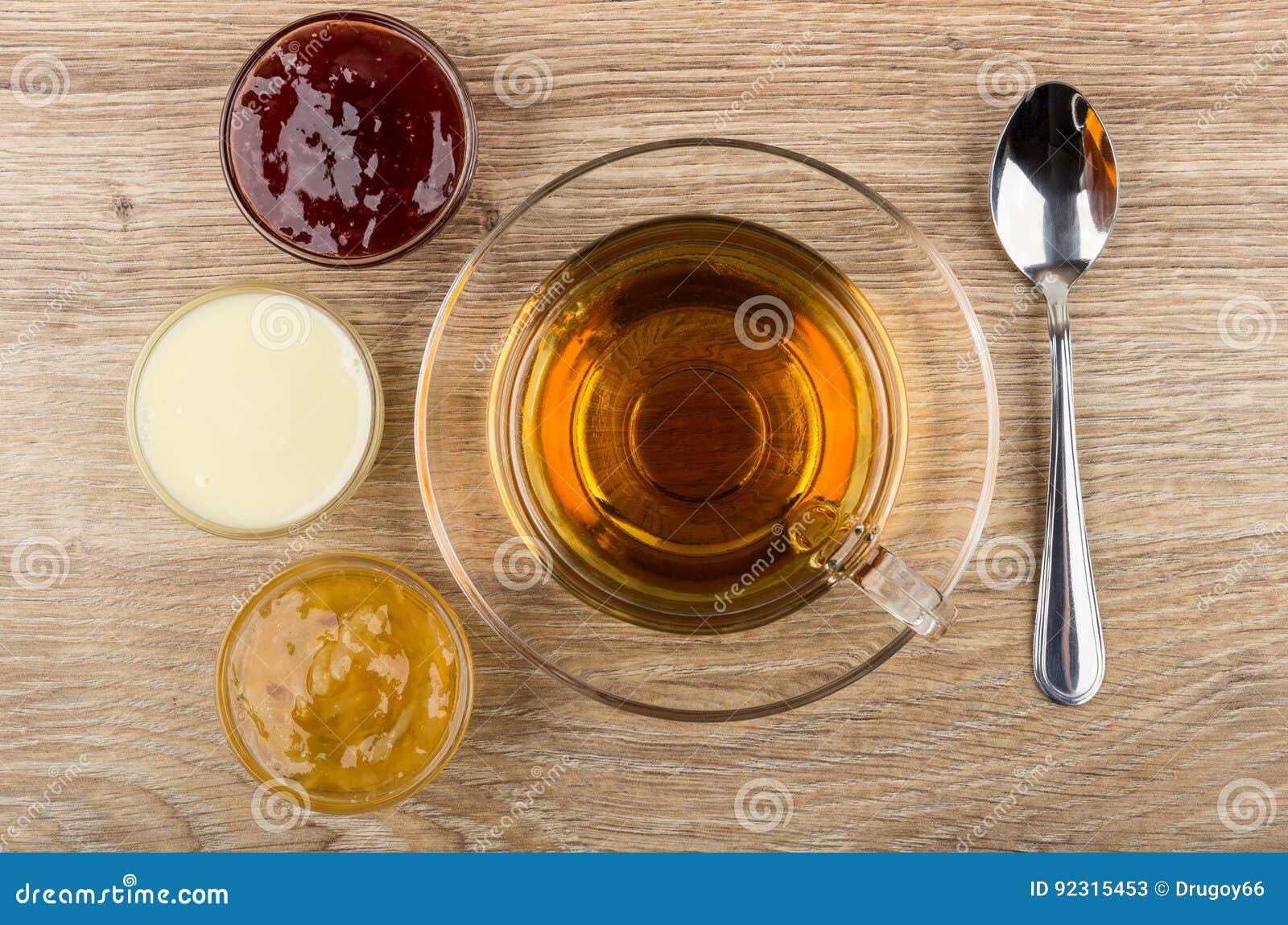 Copo do chá, bacias com doce, leite condensado e colher de chá