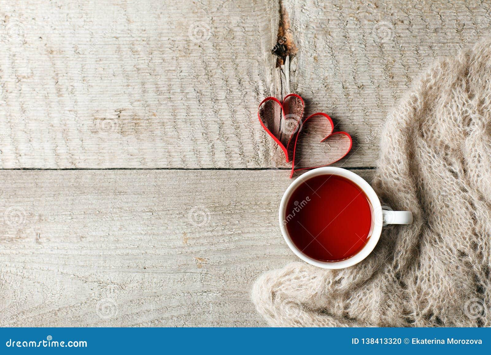 Copo do chá com forma do coração e lenço de lã morno da manta da camiseta na tabela de madeira do vintage, conceito mínimo do dia