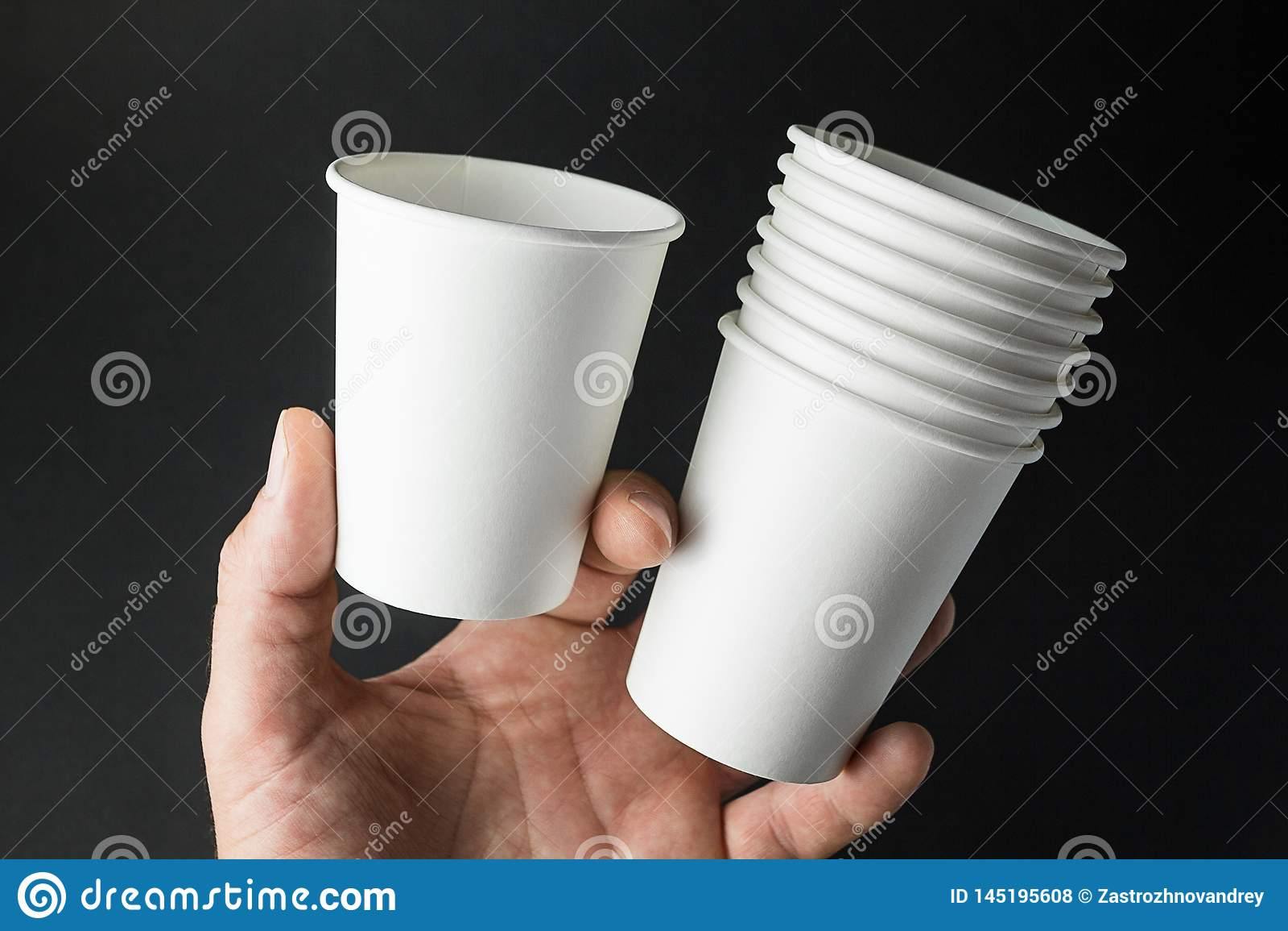 Copo do Livro Branco para a soda, o suco, o chá e o café na mão do homem Espaço para o texto, modelo