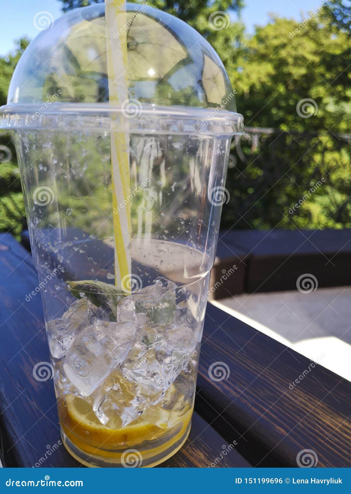 Copo plástico com os restos da limonada na tabela fora