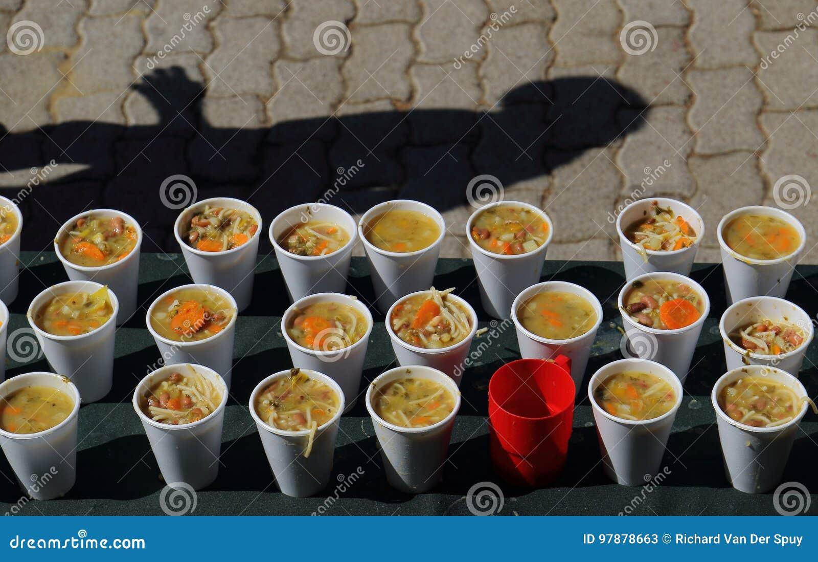 Copos da sopa em uma cozinha de sopa para os pobres