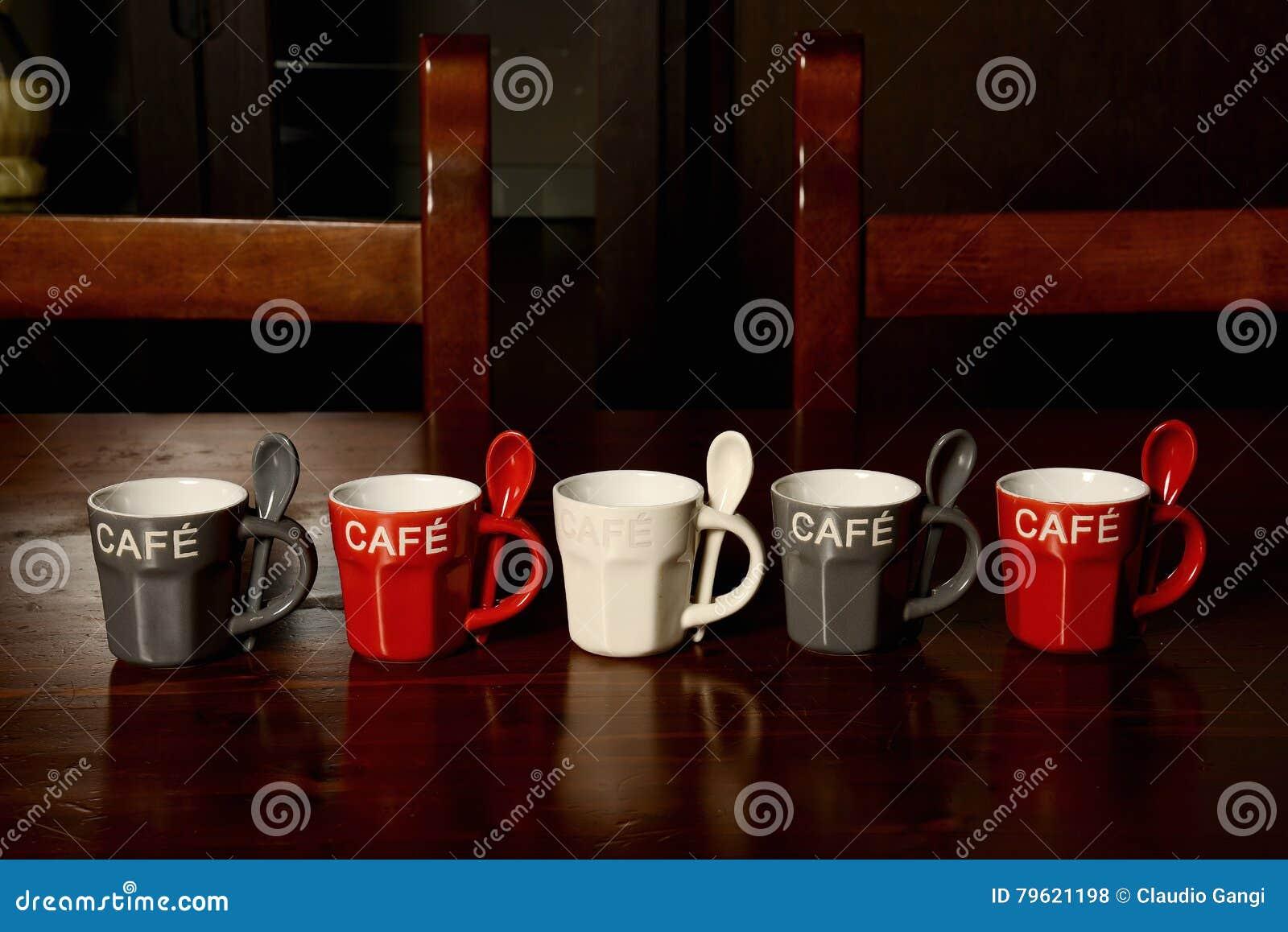 Copos de café coloridos na tabela de madeira