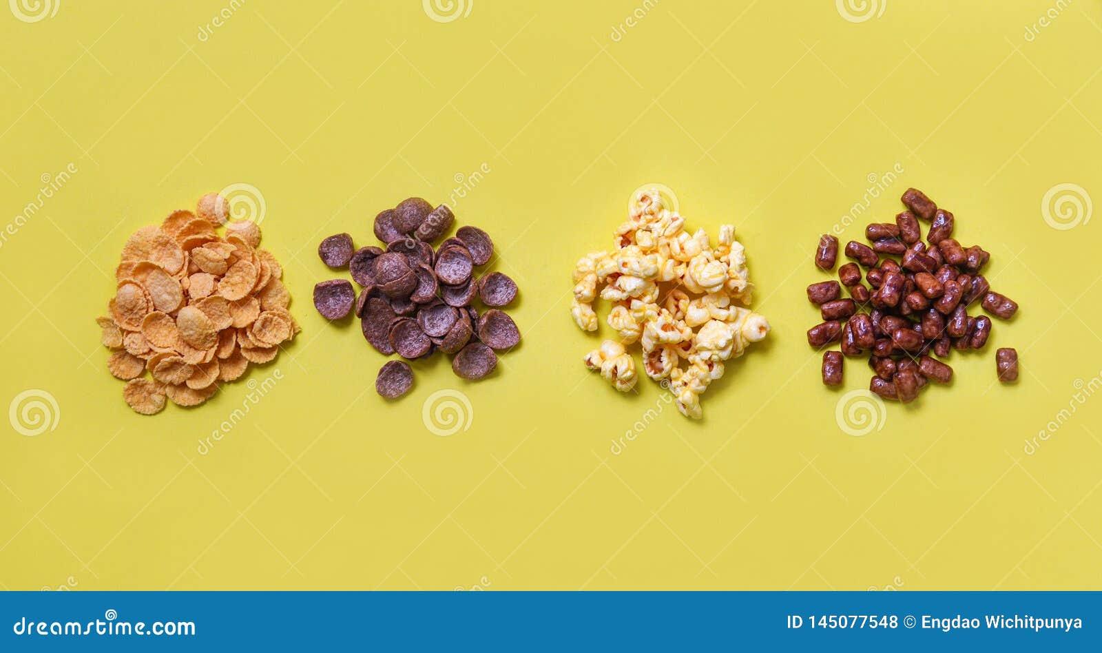 Copos de maíz bocado de los diversos cereales y pila de las palomitas en la opinión superior del fondo amarillo para el desayun