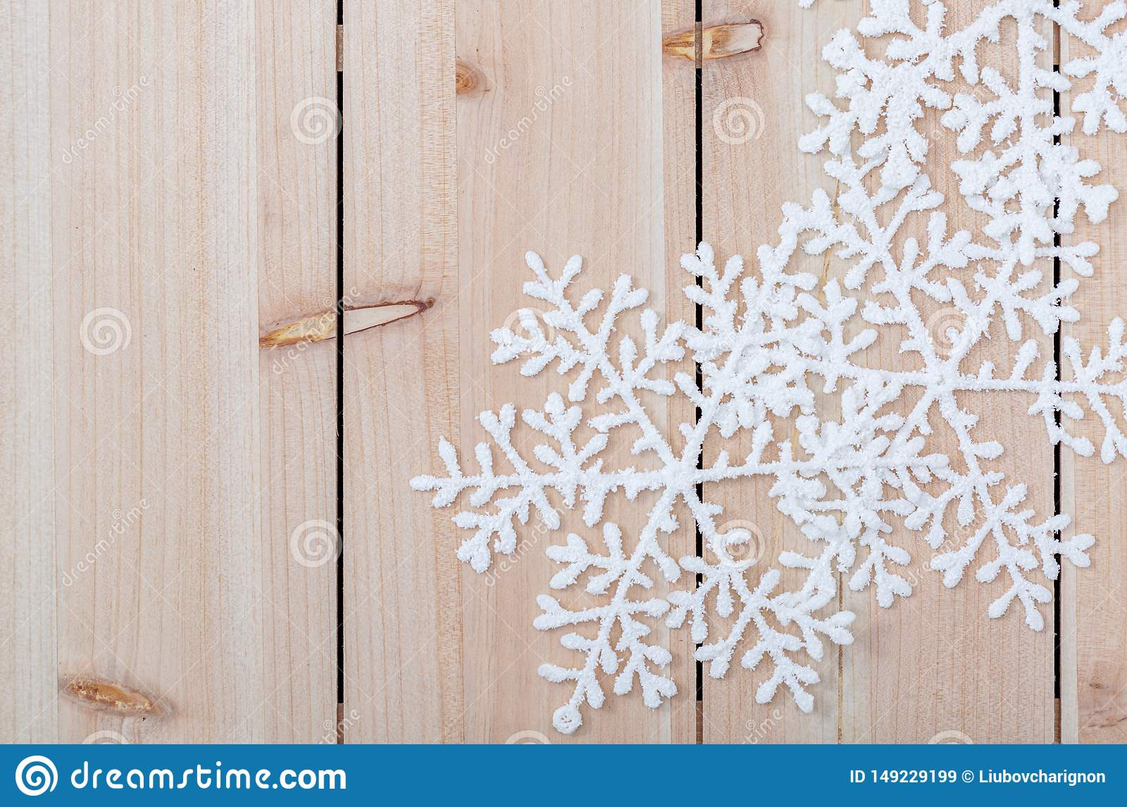 Copos de nieve artificiales blancos en una tabla de madera ligera Fondo de la decoraci?n de la Navidad y espacio de la copia para