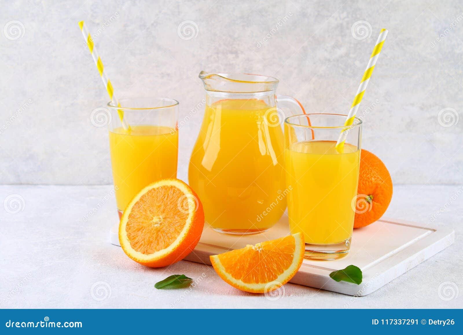 Copos de vidro e um jarro do suco de laranja fresco com fatias de tubos alaranjados e amarelos em uma luz - tabela cinzenta
