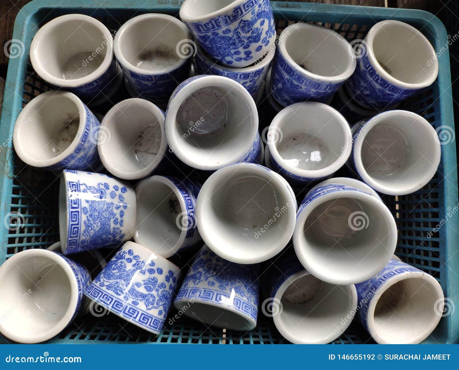 Copos do estilo chinês usados bebendo o chá colocado na cesta azul