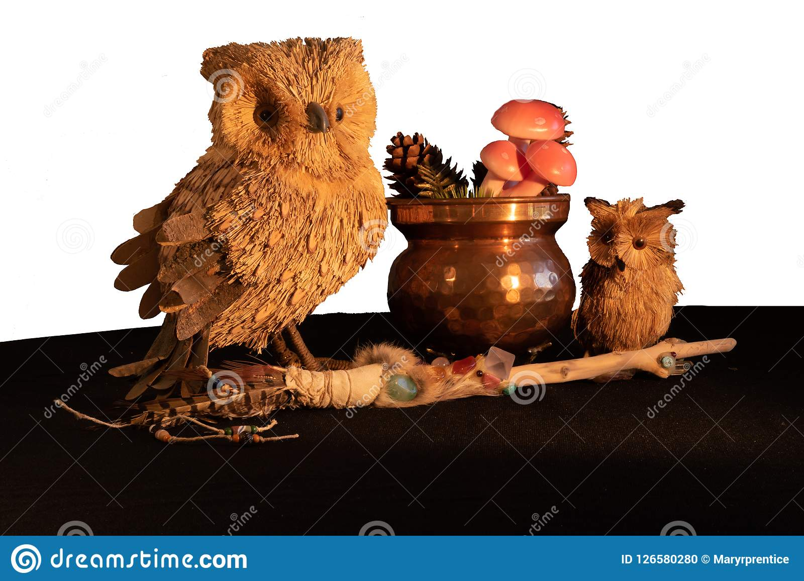 Copper cauldron with mushrooms and pine cones, a magic wand with quartz and amethyst crystals and an owl mother and child made fro