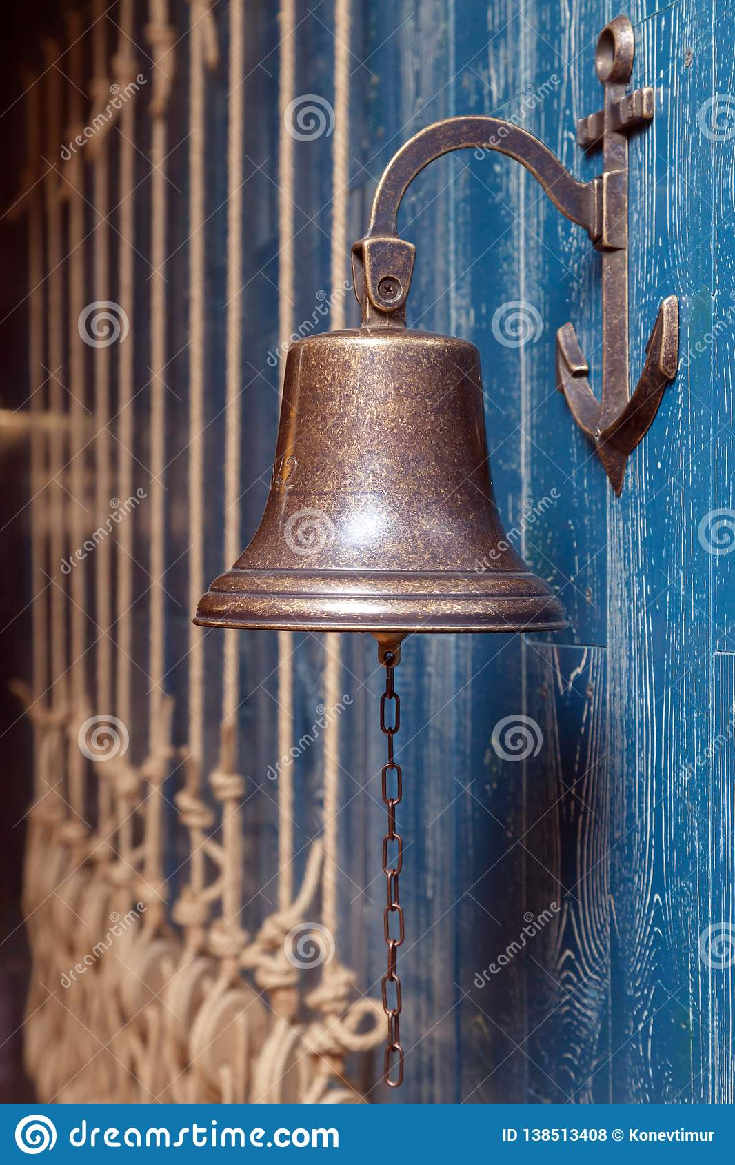 Copper old vintage bell, doorbell, rope on a wooden blue aged wall. Concept decor element in interior of deck, cabin of ship,