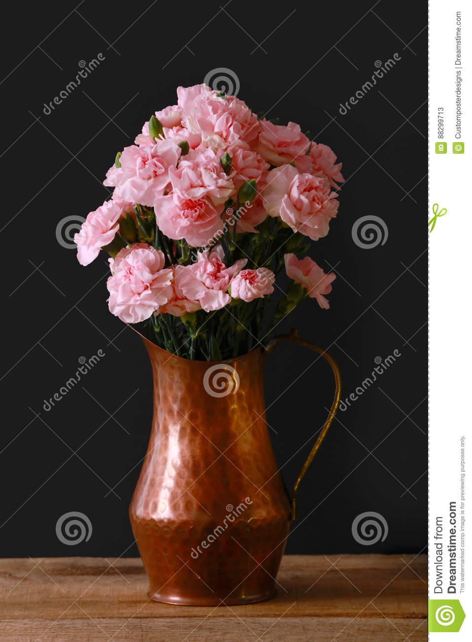 A copper vase on a black background with pink miniature carnations.