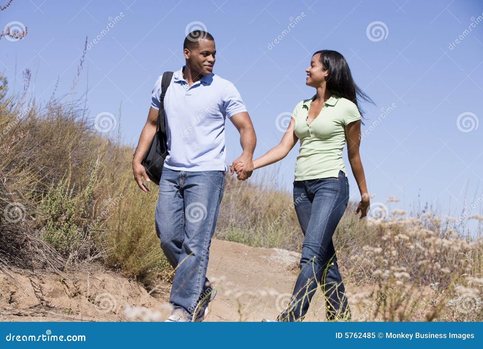 Coppia camminare sulle mani della holding del percorso e sorridere