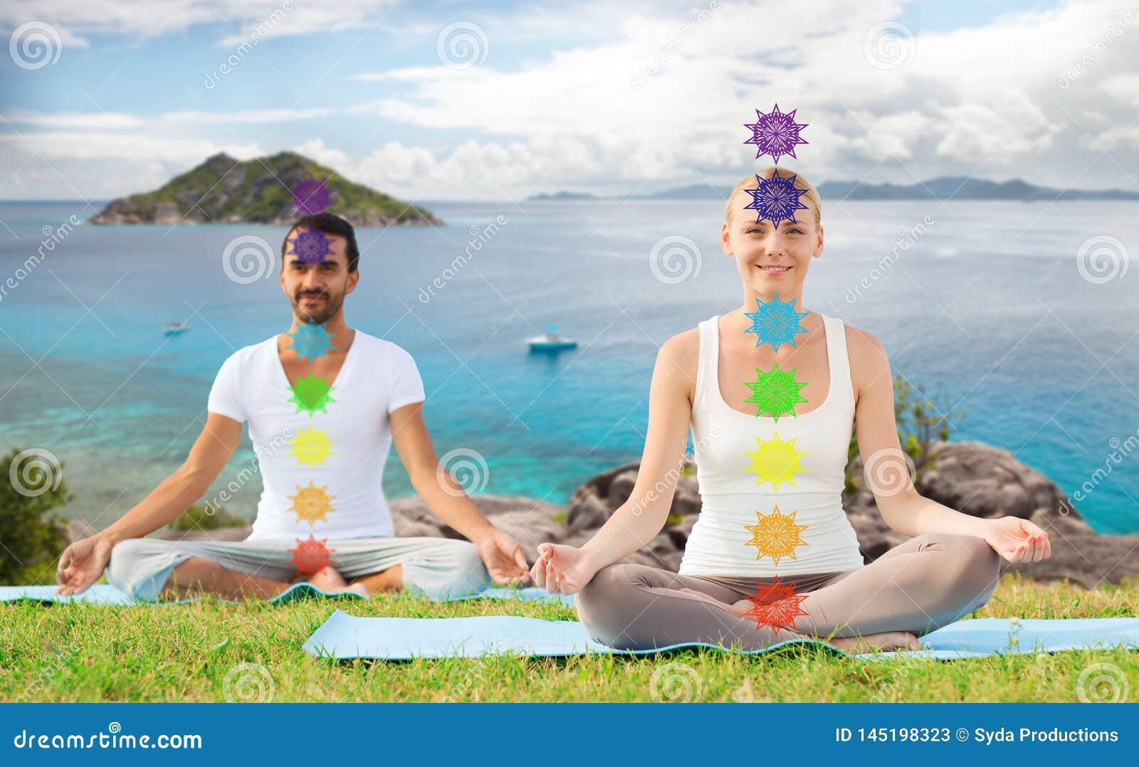 Coppia fare l yoga nella posa del loto con sette chakras