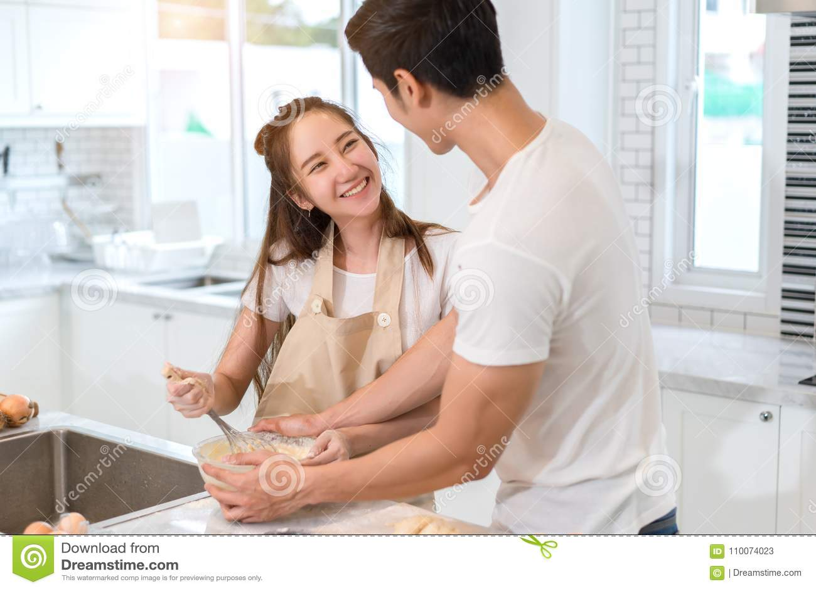 Coppia la cottura del forno nella stanza della cucina, in giovane uomo asiatico ed in donna insieme