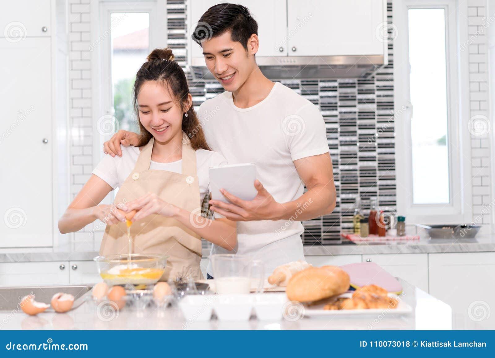 Coppia la fabbricazione il forno, il dolce nella stanza della cucina, il giovane uomo asiatico e della donna