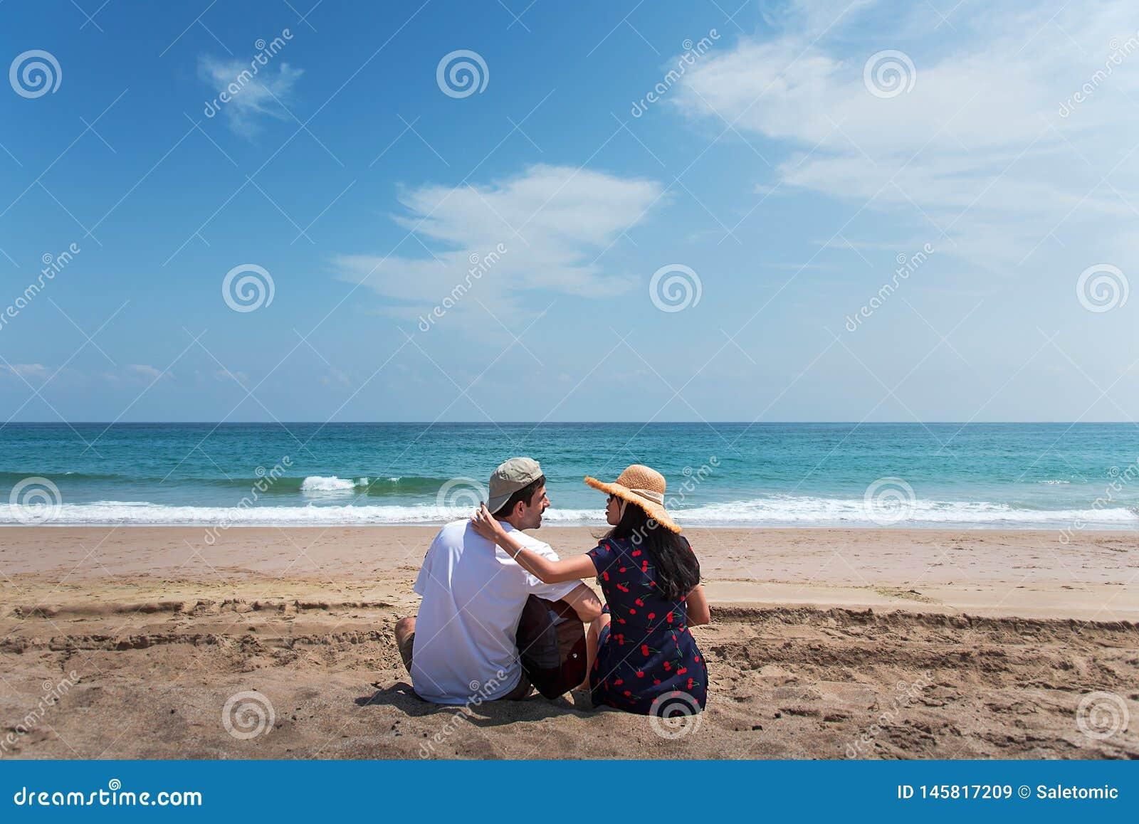 Coppia spendere il tempo sulla spiaggia con una chitarra