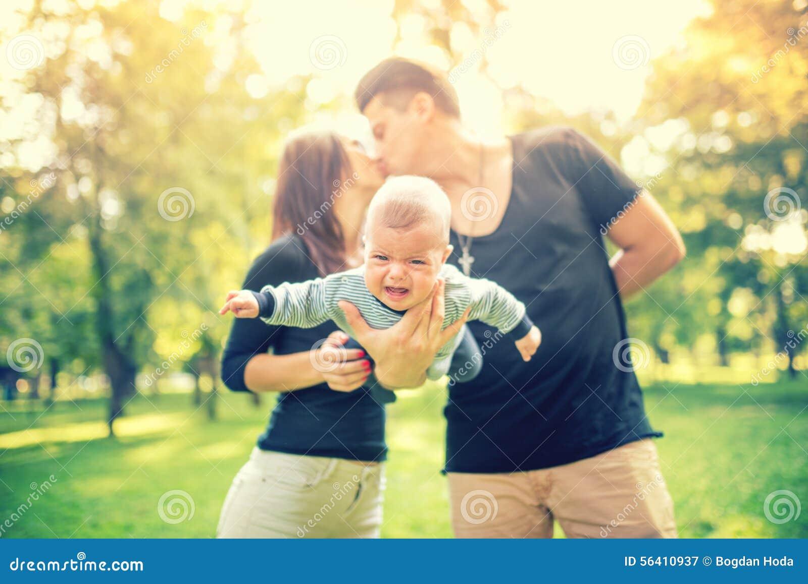 Coppia sposata che tiene bambino neonato e baciare Famiglia felice, concetto del giorno del padre e madre