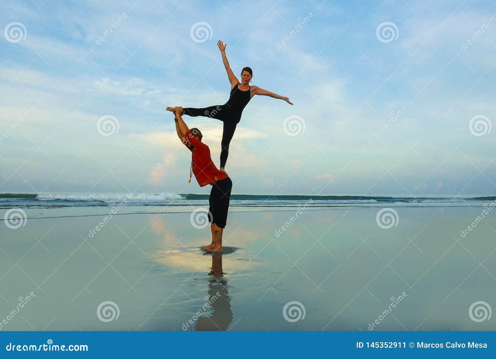 Coppie adatte sane ed attraenti degli acrobate che fanno l equilibrio di acroyoga ed esercizio di meditazione sulla bella pratica