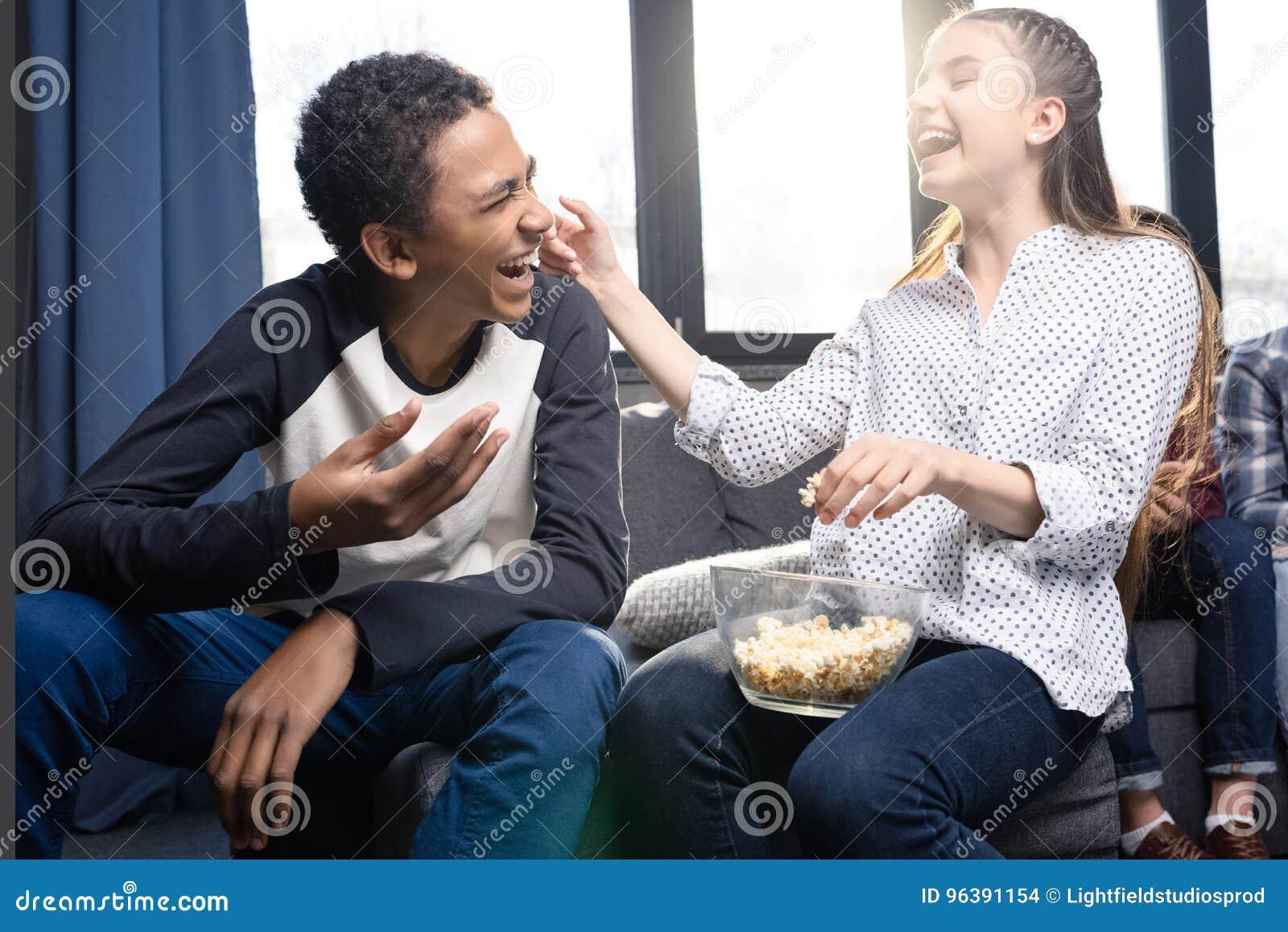 Coppie adolescenti felici che mangiano popcorn dalla ciotola di vetro all interno