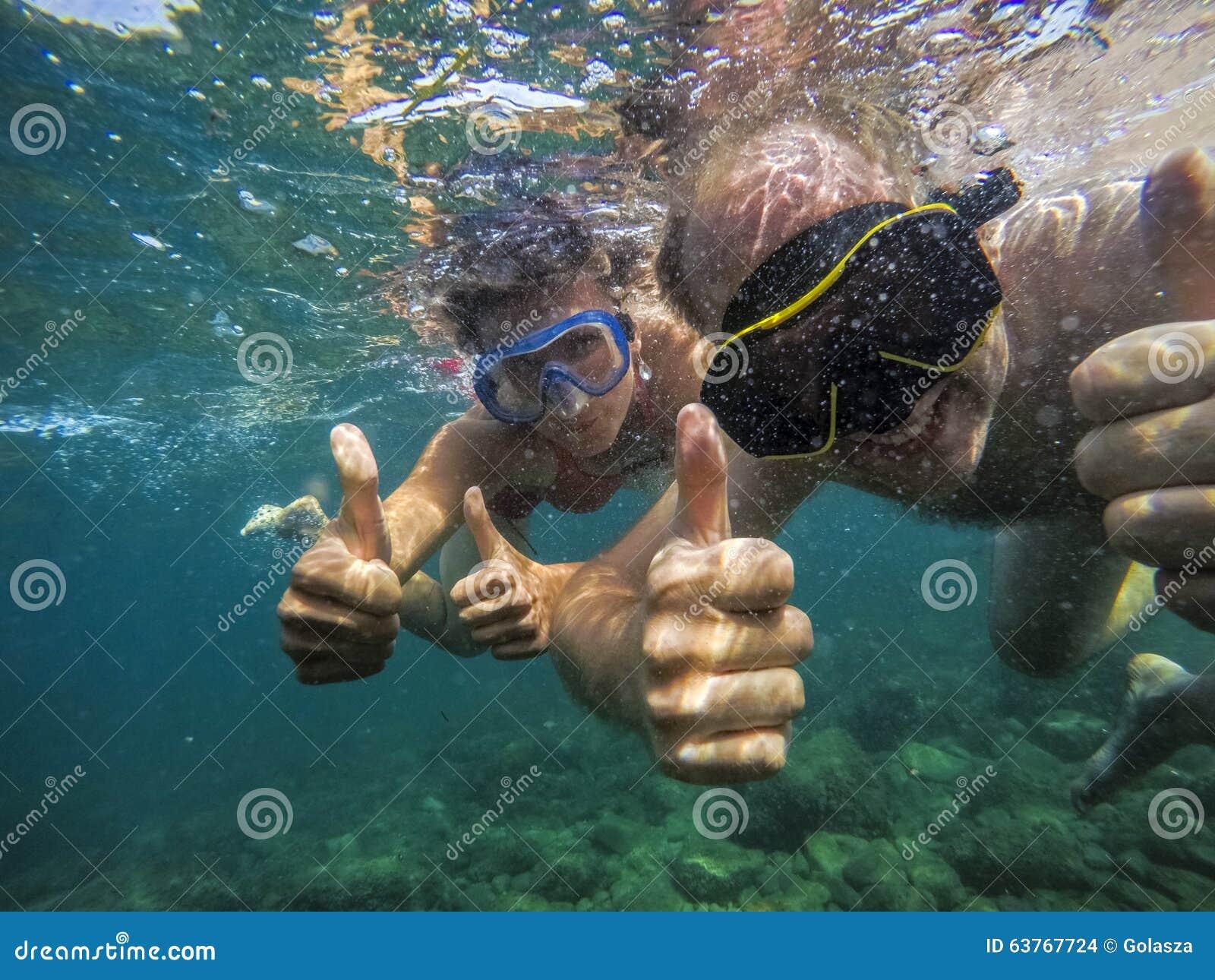 Coppie allegro che nuotano underwater nel mare