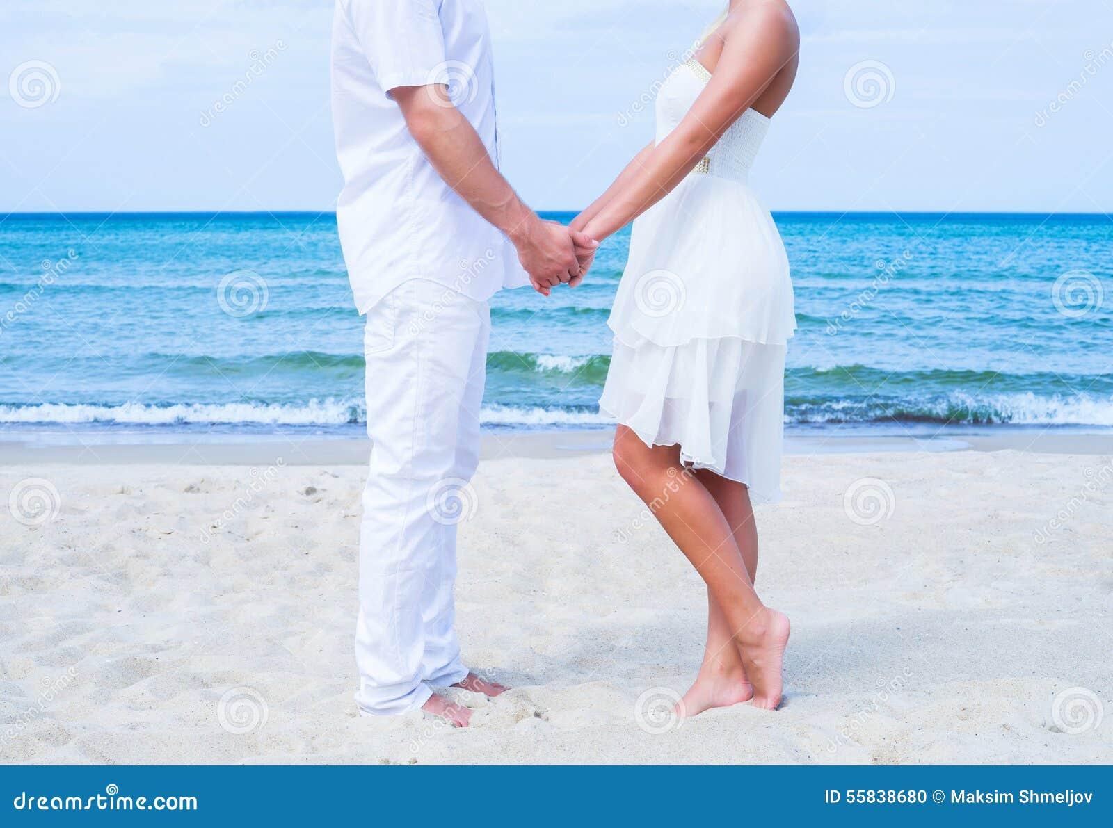Coppie amorose che camminano e che abbracciano su una spiaggia di estate