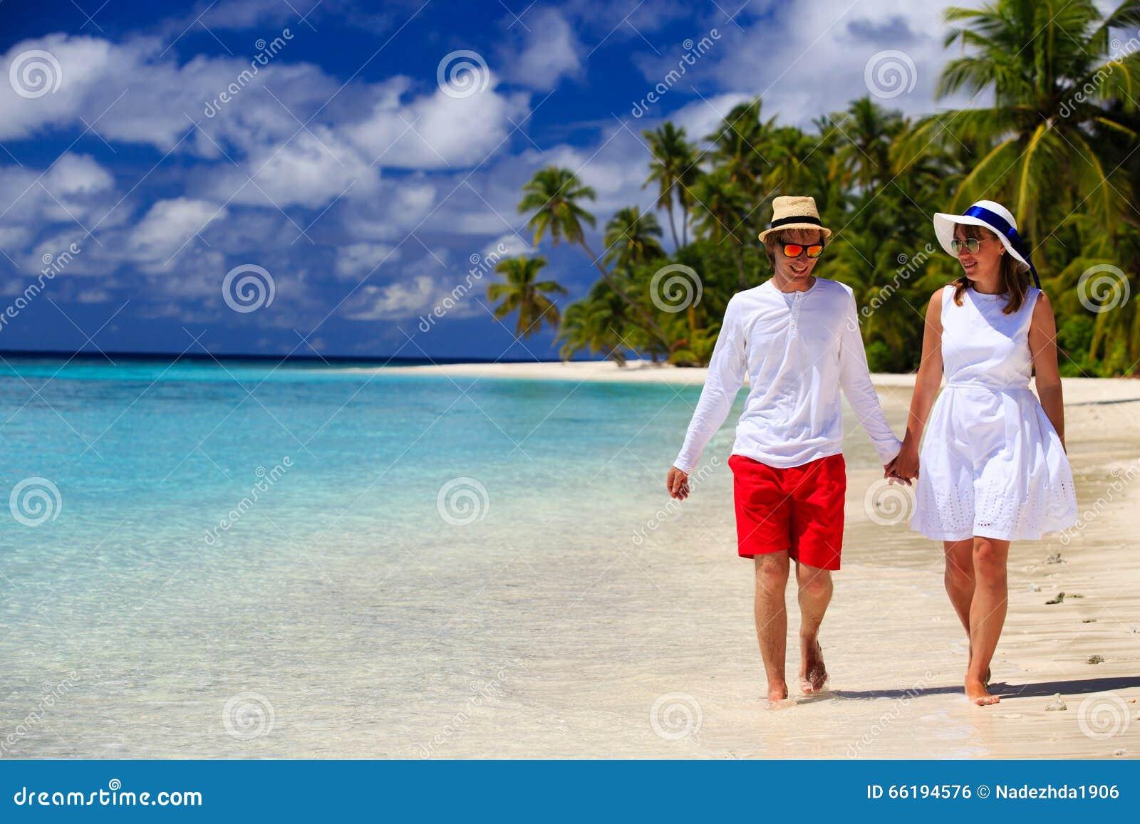 Coppie amorose felici che camminano sulla spiaggia tropicale