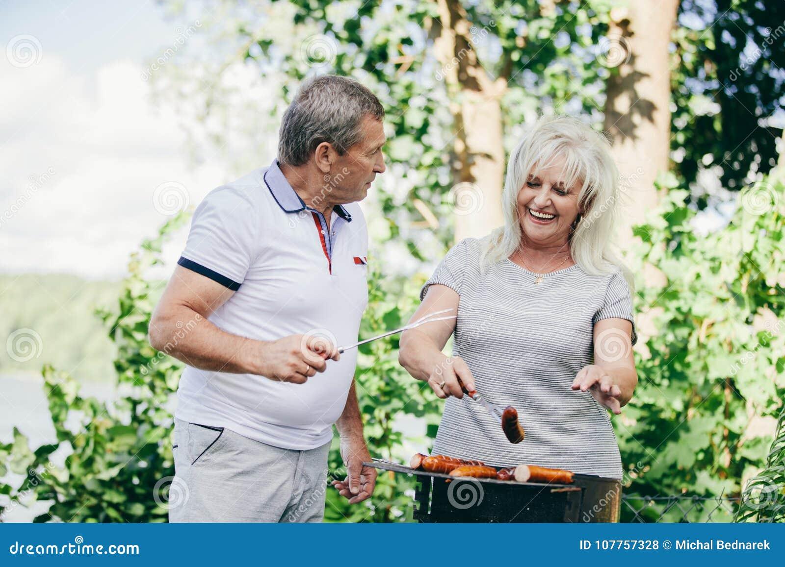 Coppie anziane felici che barbequing insieme