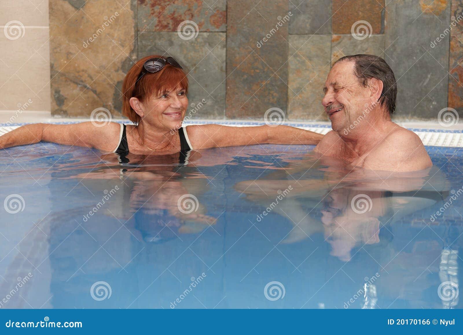 Coppie anziane a sorridere del raggruppamento dell acqua calda