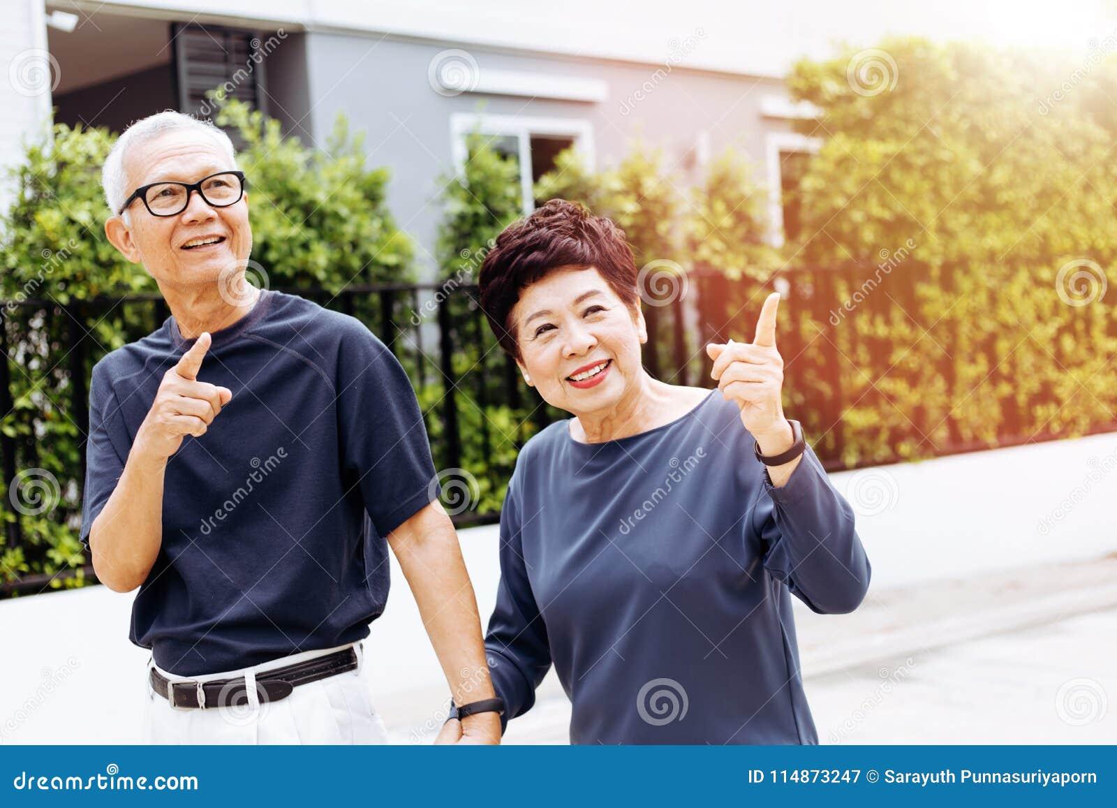 Coppie asiatiche senior felici che camminano e che indicano nel parco e nella casa all aperto Tono caldo con luce solare