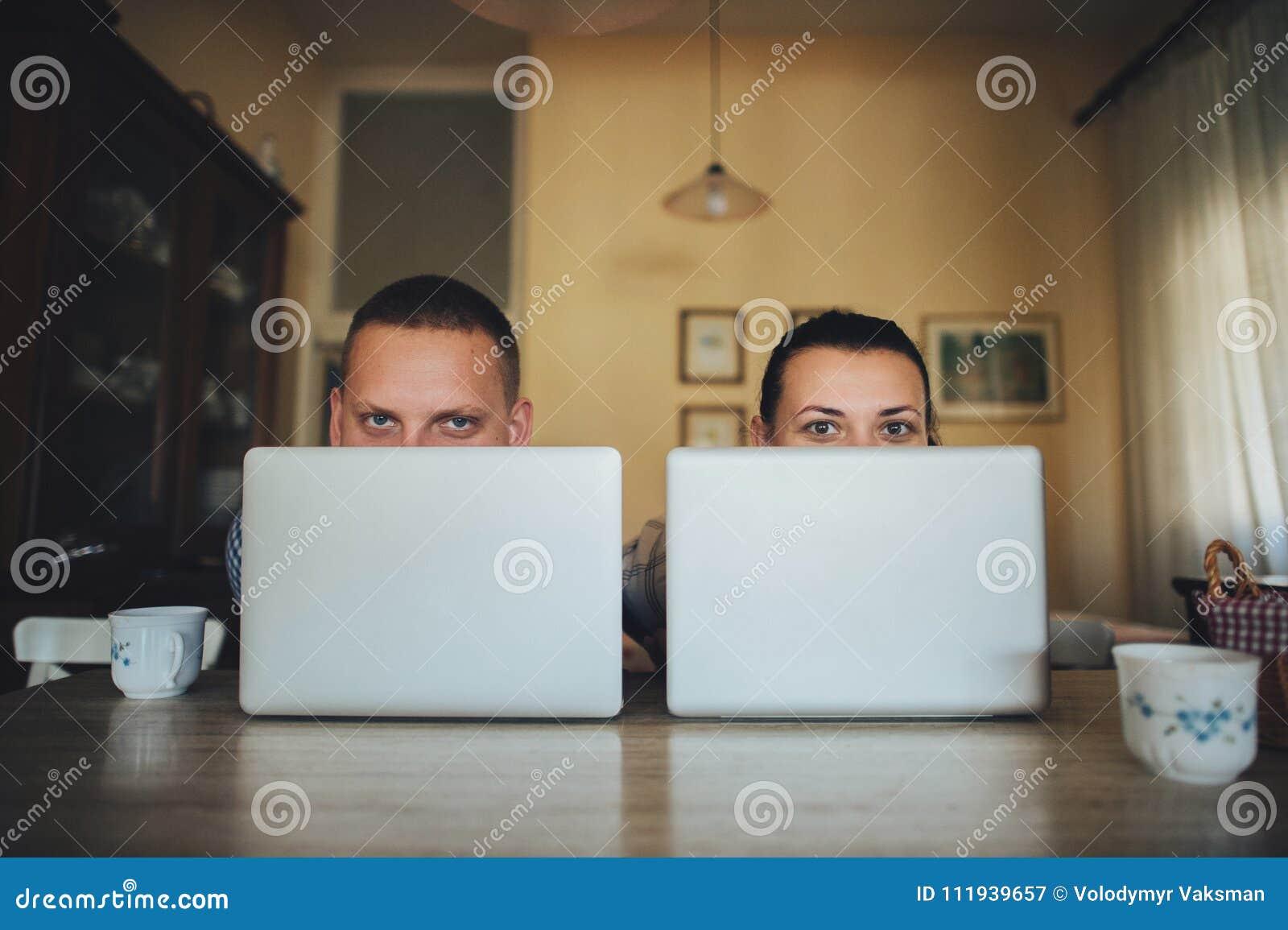 Coppie attraenti facendo uso del computer portatile insieme sul sofà da comperare online a