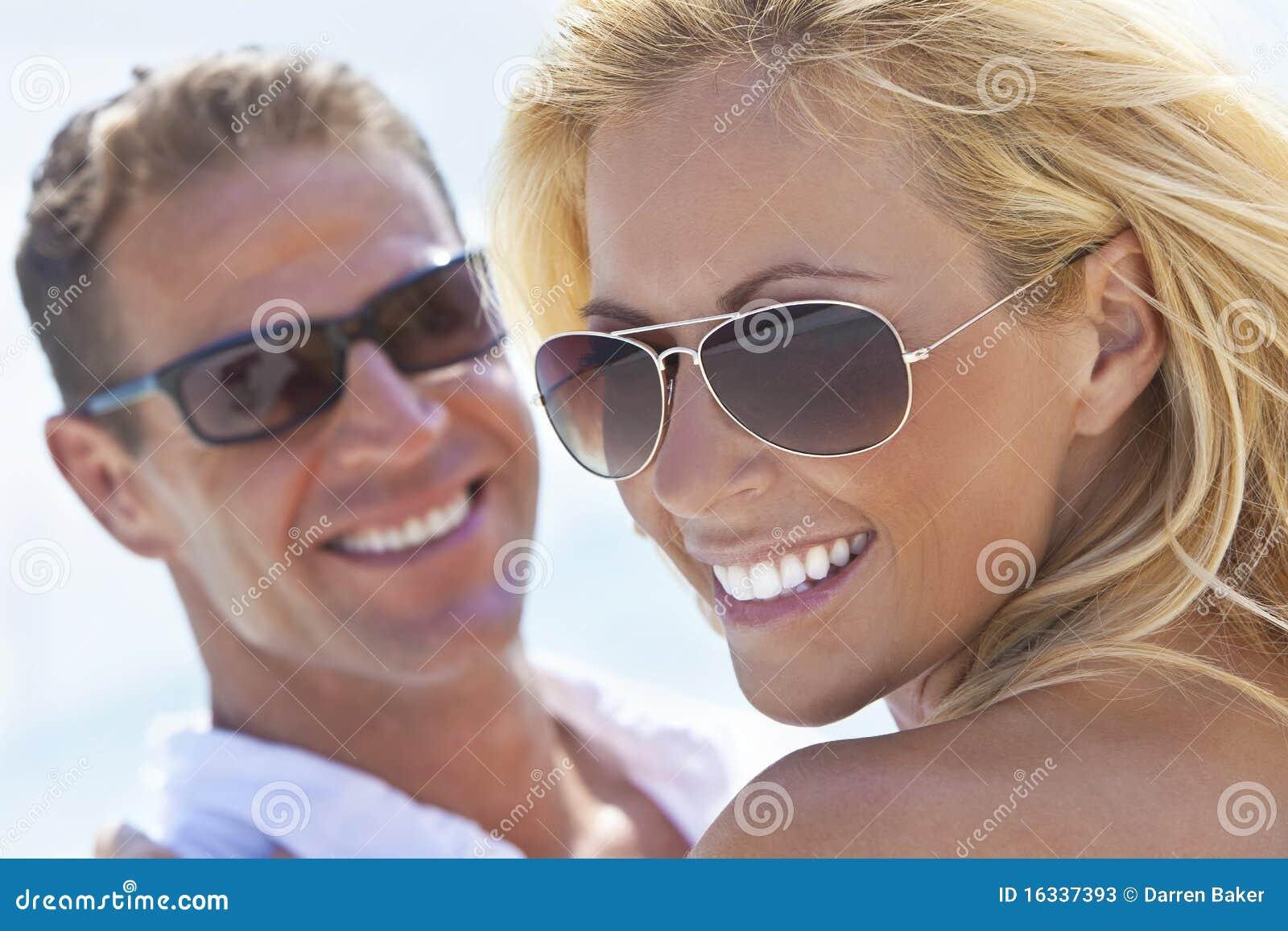 Coppie attraenti felici dell uomo e della donna alla spiaggia