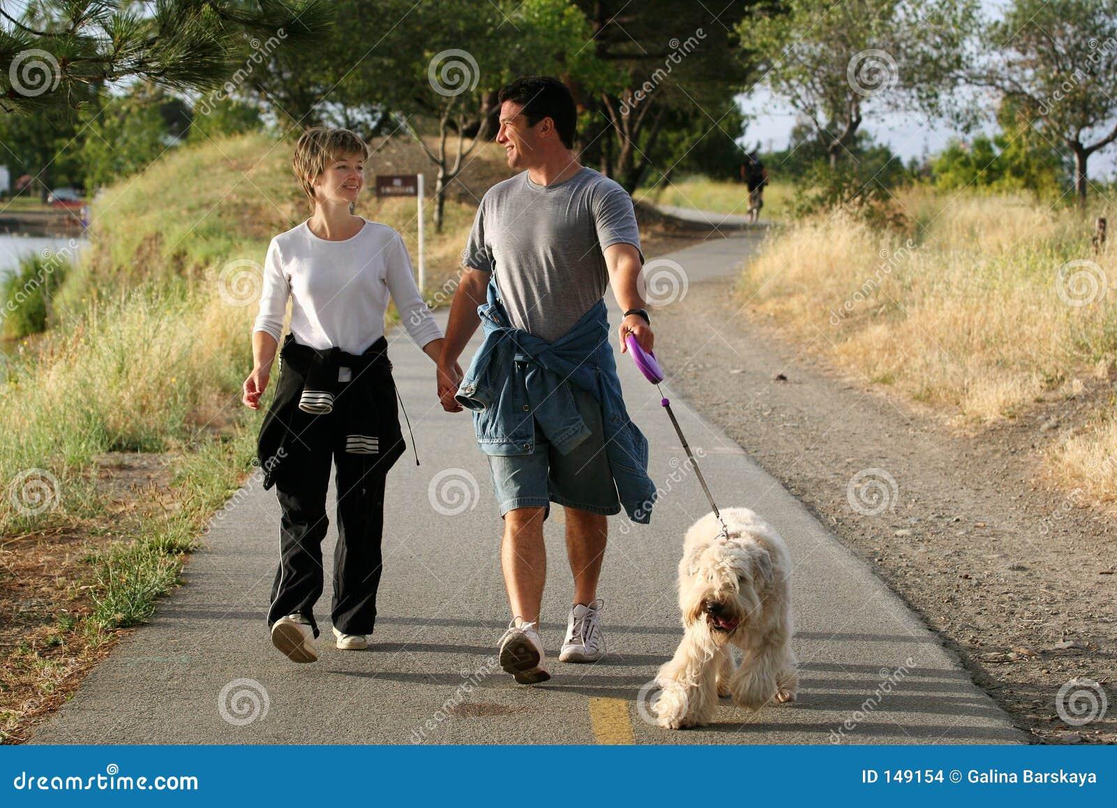 Coppie che camminano il loro cane