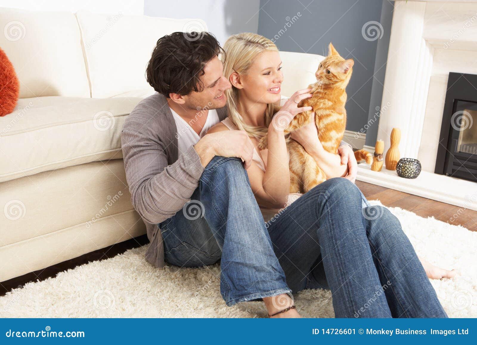 Coppie che catturano gioco con il gatto dell animale domestico nel paese