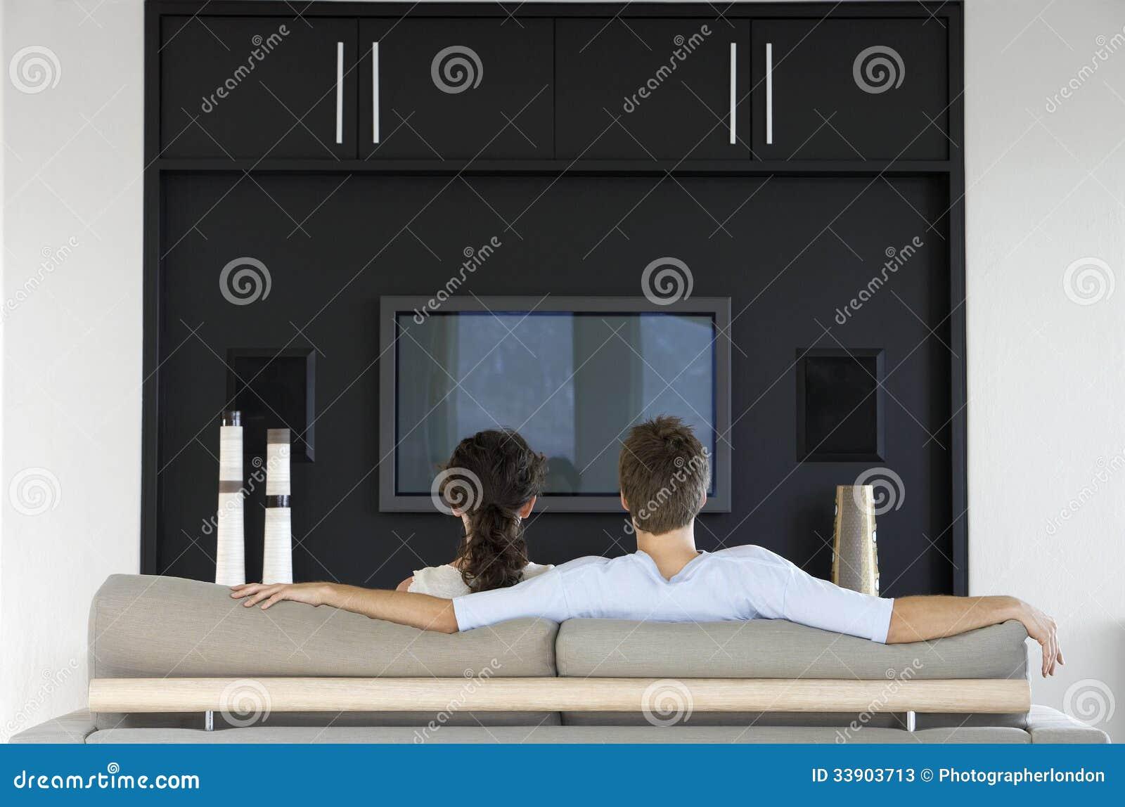 Coppie che guardano insieme TV nel salone
