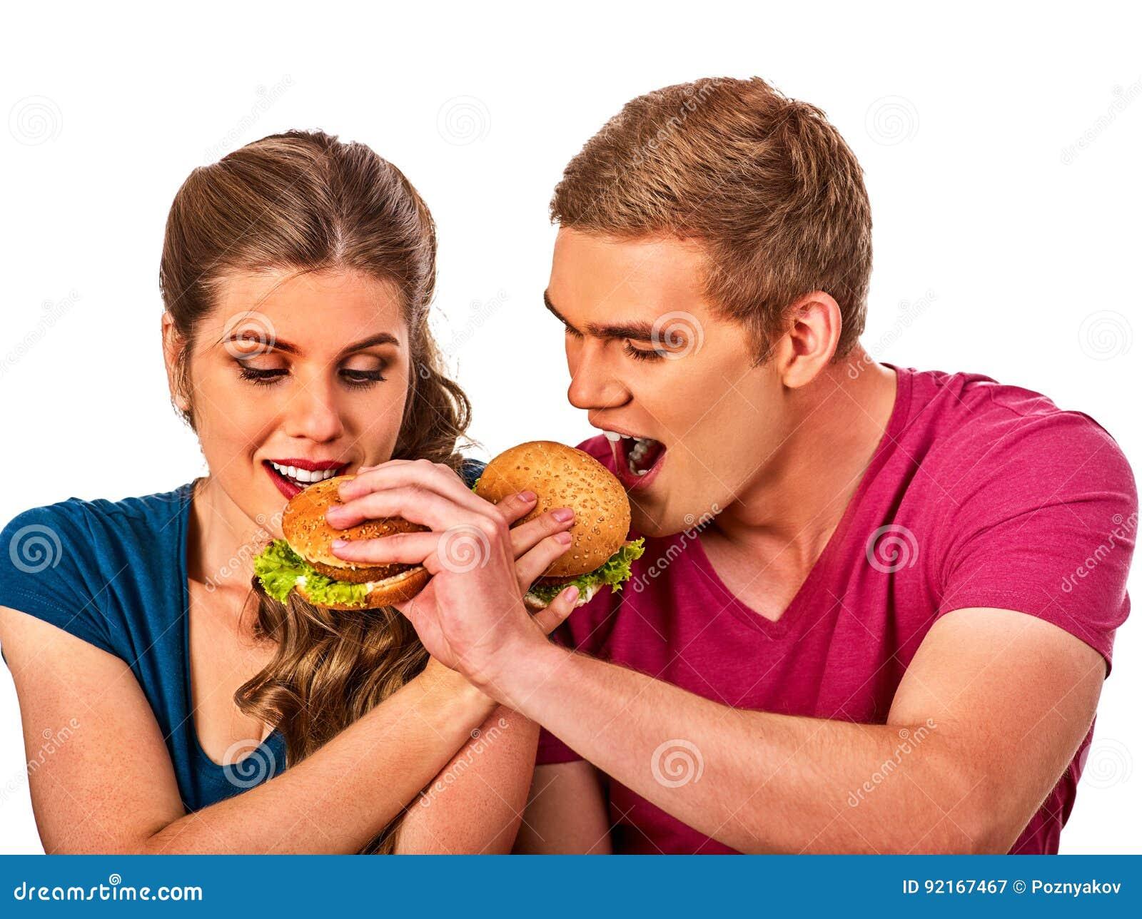 Coppie che mangiano alimenti a rapida preparazione L uomo e la donna mangiano l hamburger