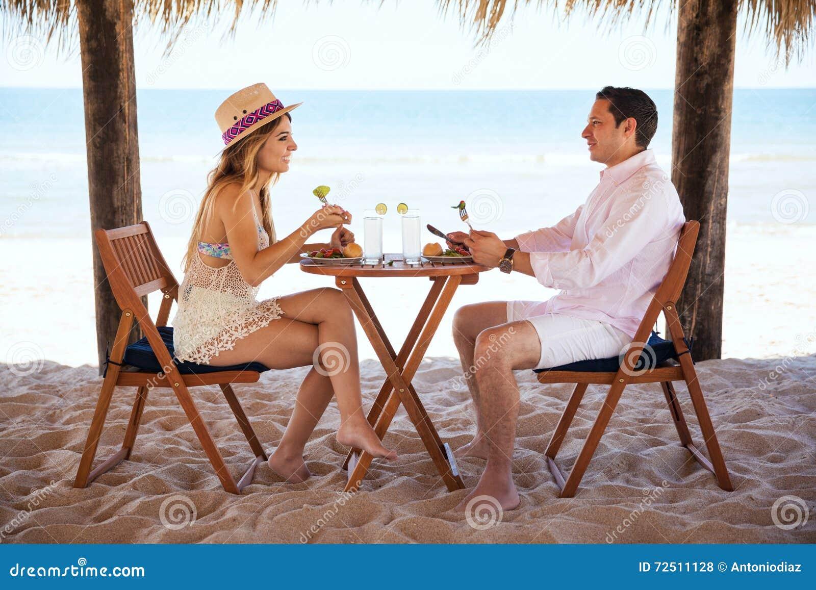Coppie che mangiano pranzo alla spiaggia