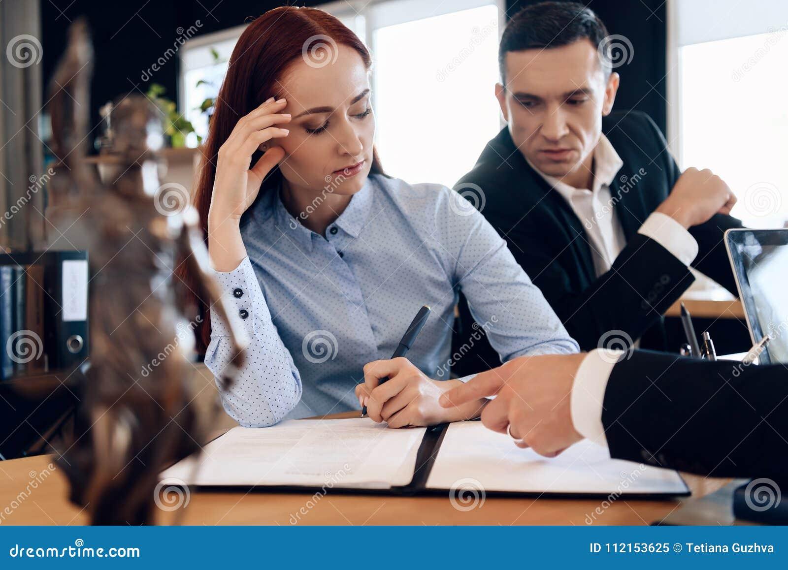 Coppie che passano attraverso le carte di firma di divorzio Il marito e la moglie adulti stanno firmando lo stabilimento di divor