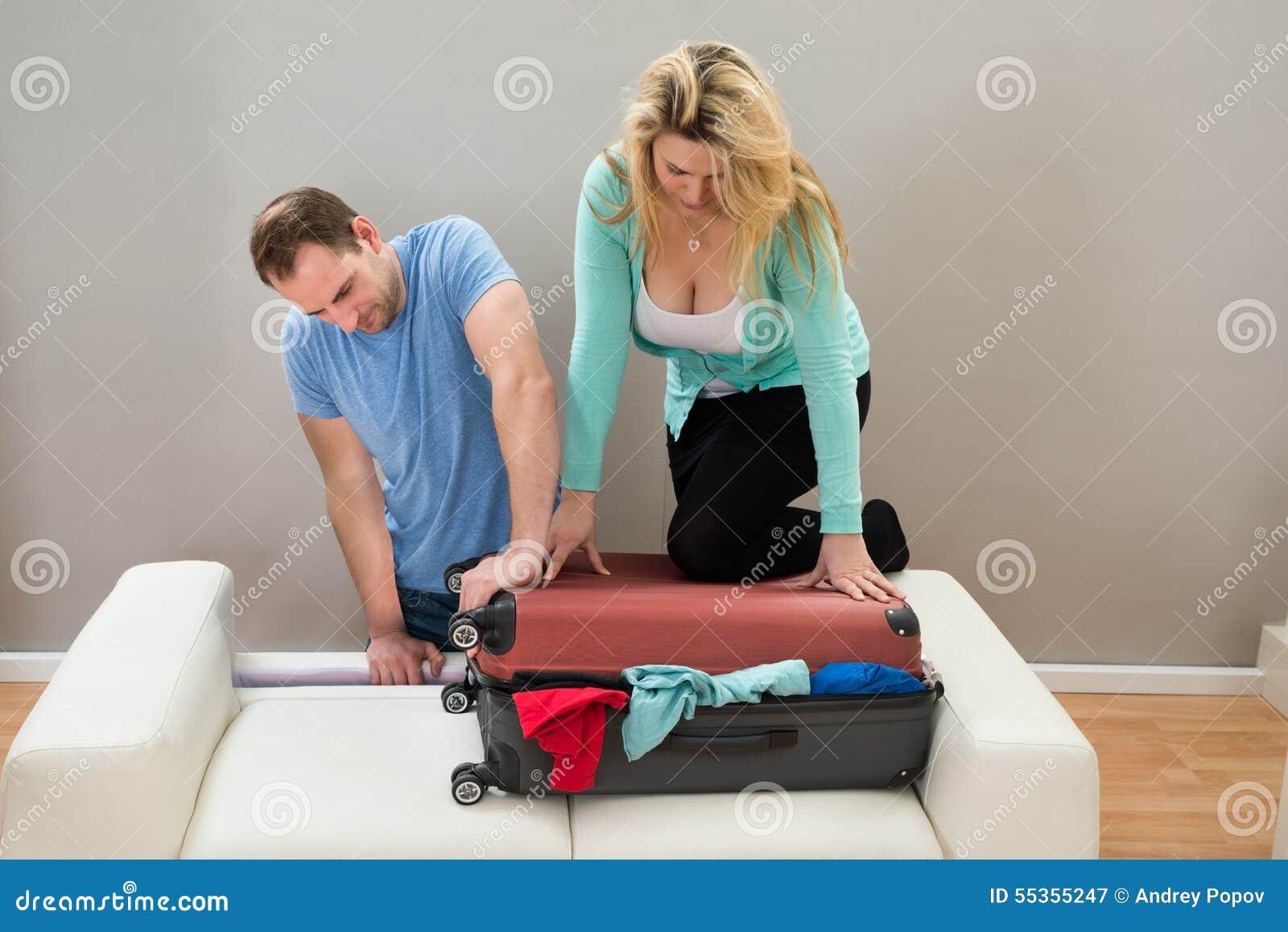 Coppie che provano a chiudere bagagli