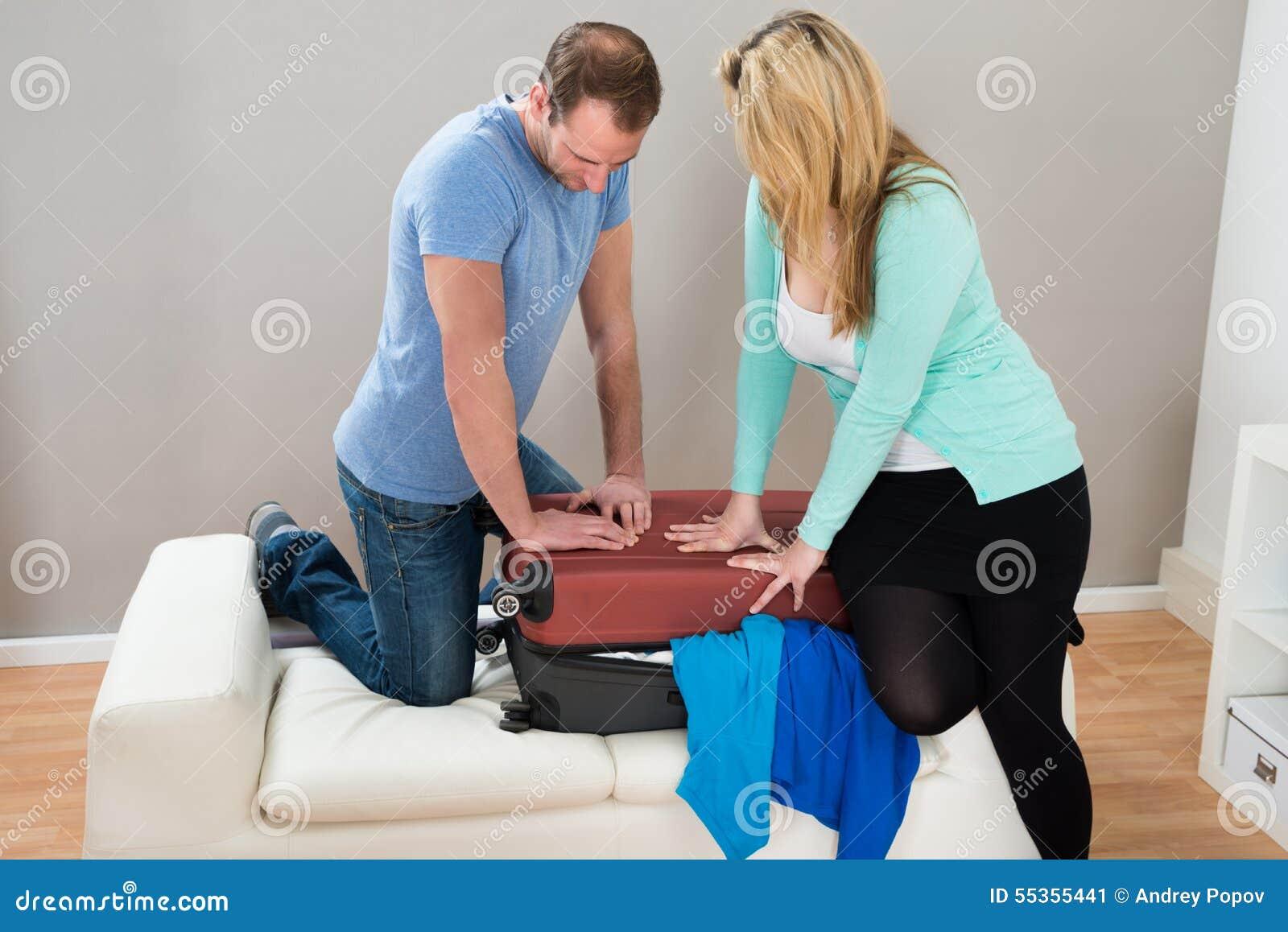 Coppie che provano a chiudere valigia a casa