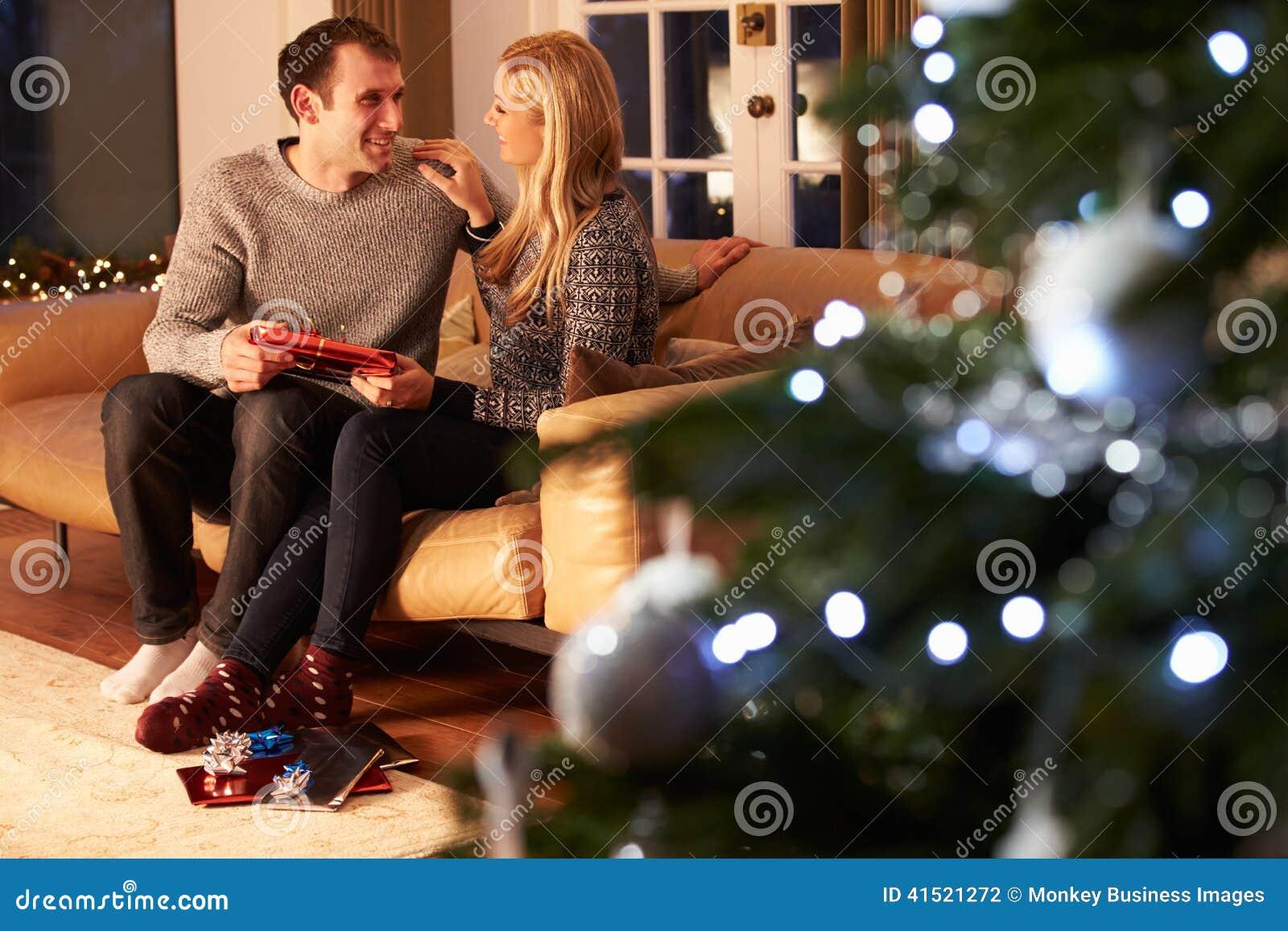 Regali Di Natale Per Coppia.Coppie Che Scambiano I Regali Dall Albero Di Natale Fotografia Stock