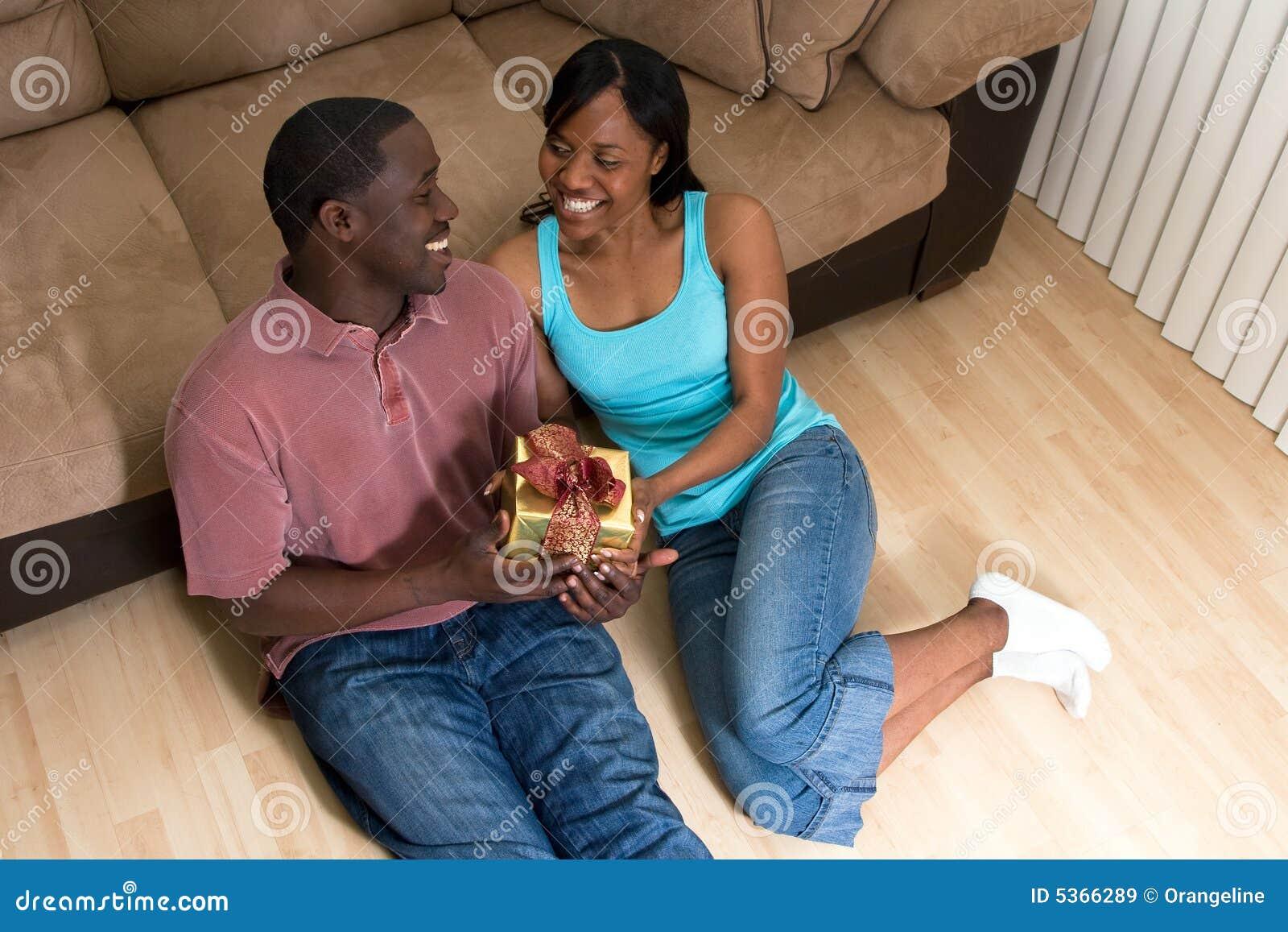 Coppie che si siedono con una Casella-Horizonta del regalo