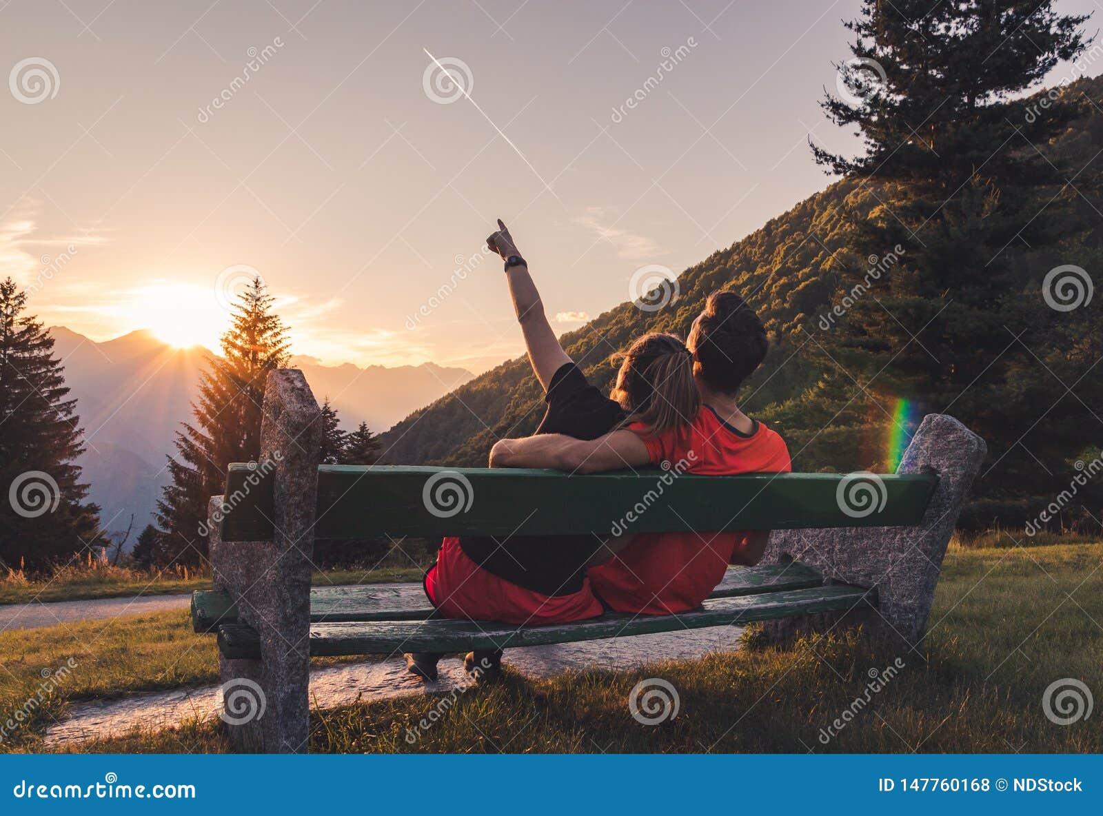 Coppie che si siedono sul banco nelle montagne che guardano il tramonto e un volo piano